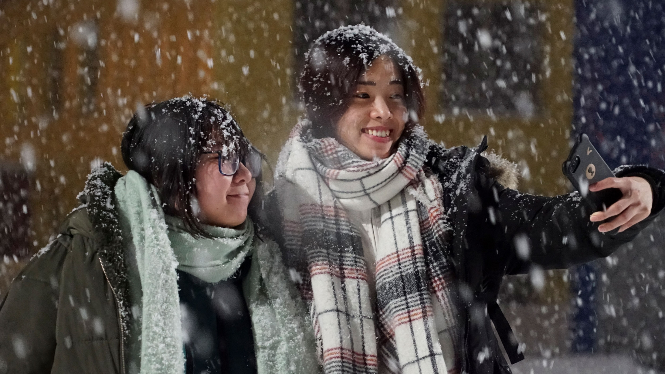 Tourists from China take a selfie as large snow flakes are falling all around them.