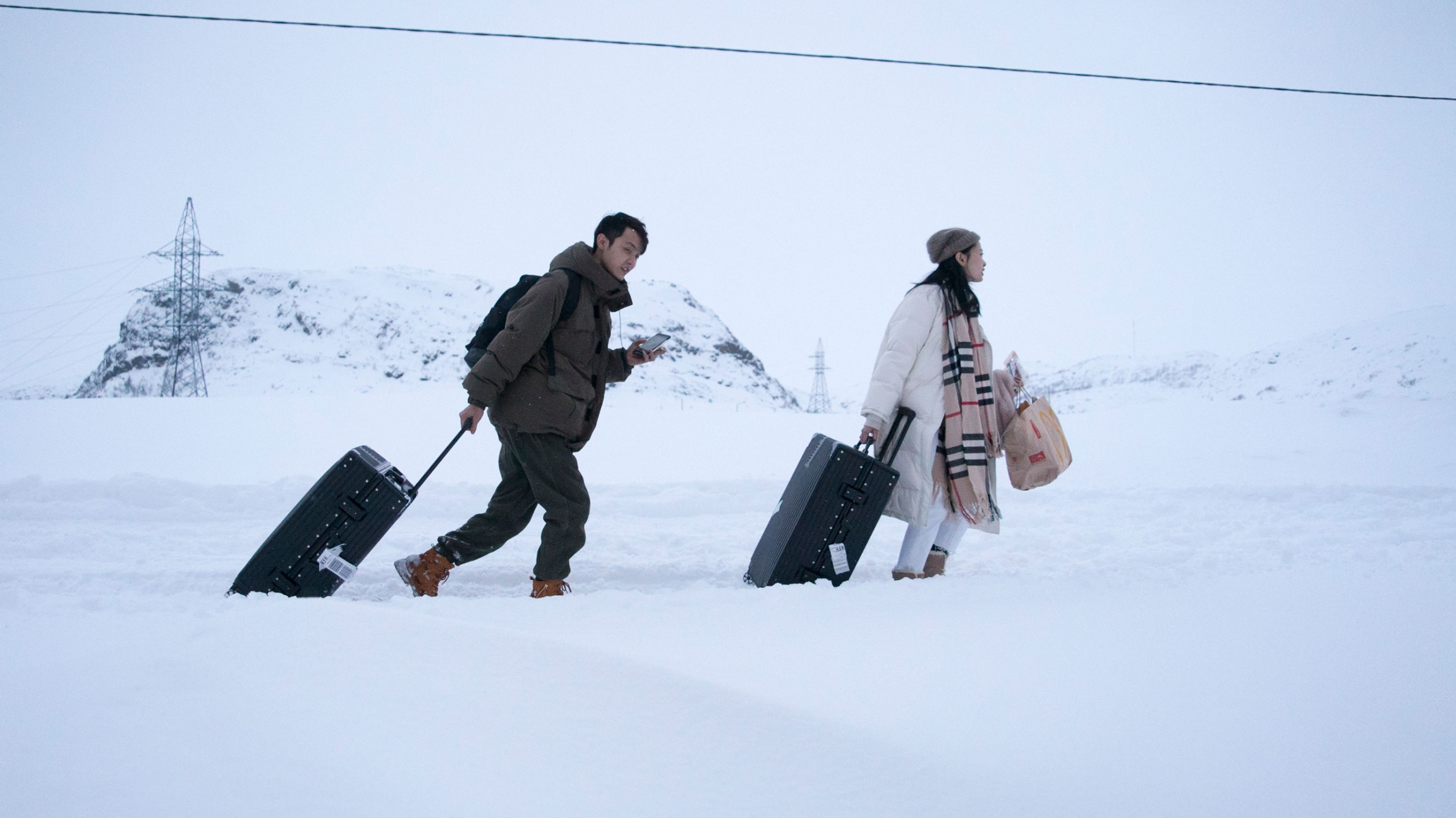 Two people are shown pulling their suitcases amongst a snowy path.