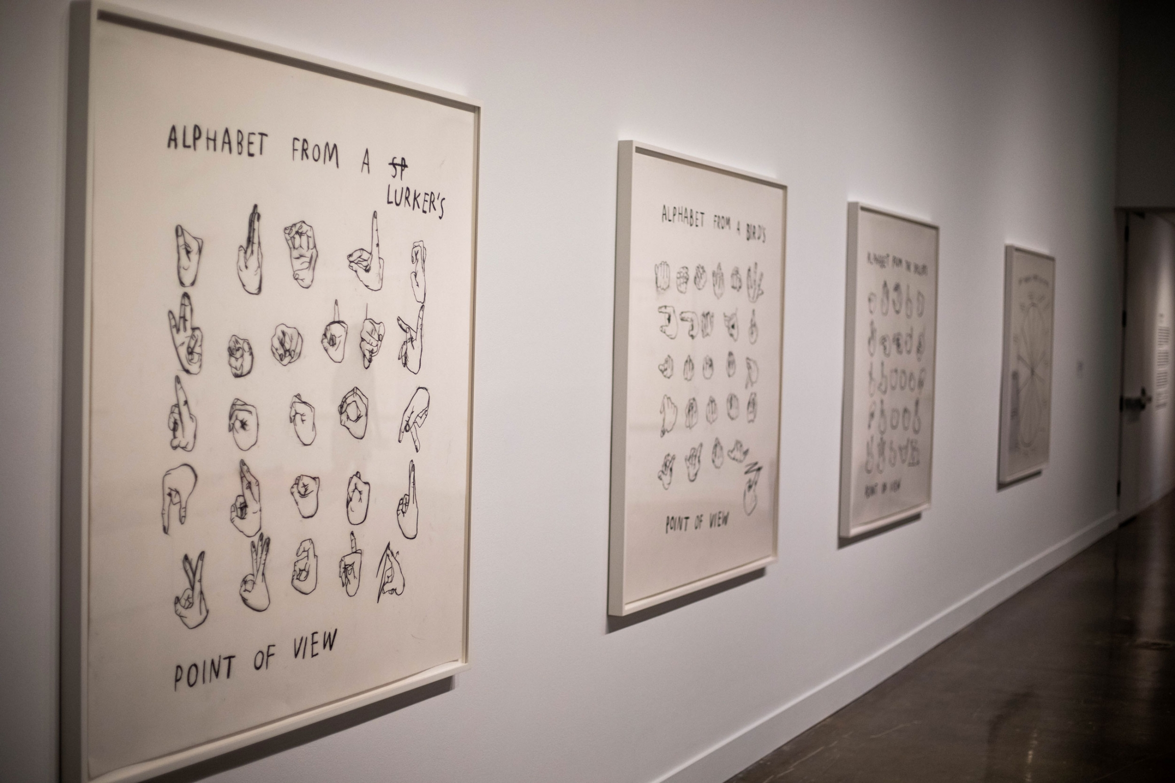 Several charcoal diagrams are shown framed and hanging on a white wall.