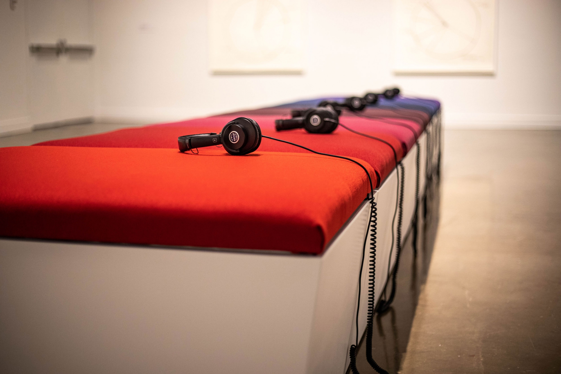 A long bench is shown with brightly colored cushions and headphones on each cushion.