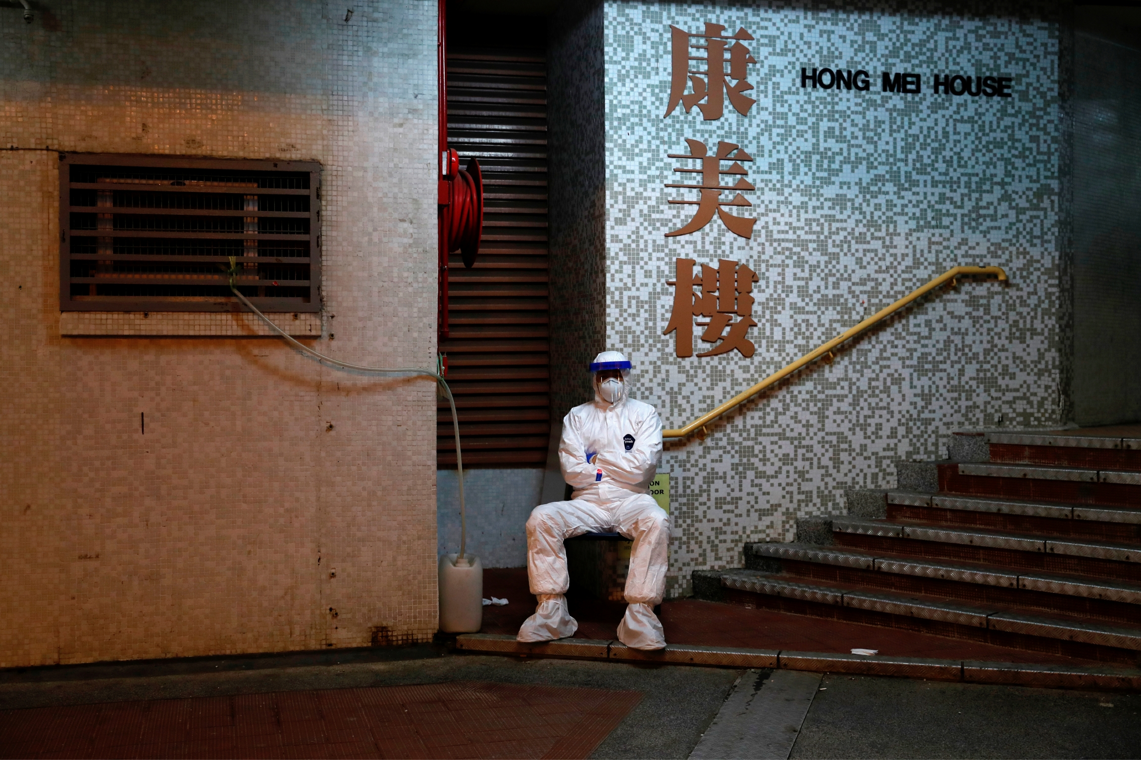 A man in protective gear sits outside a building