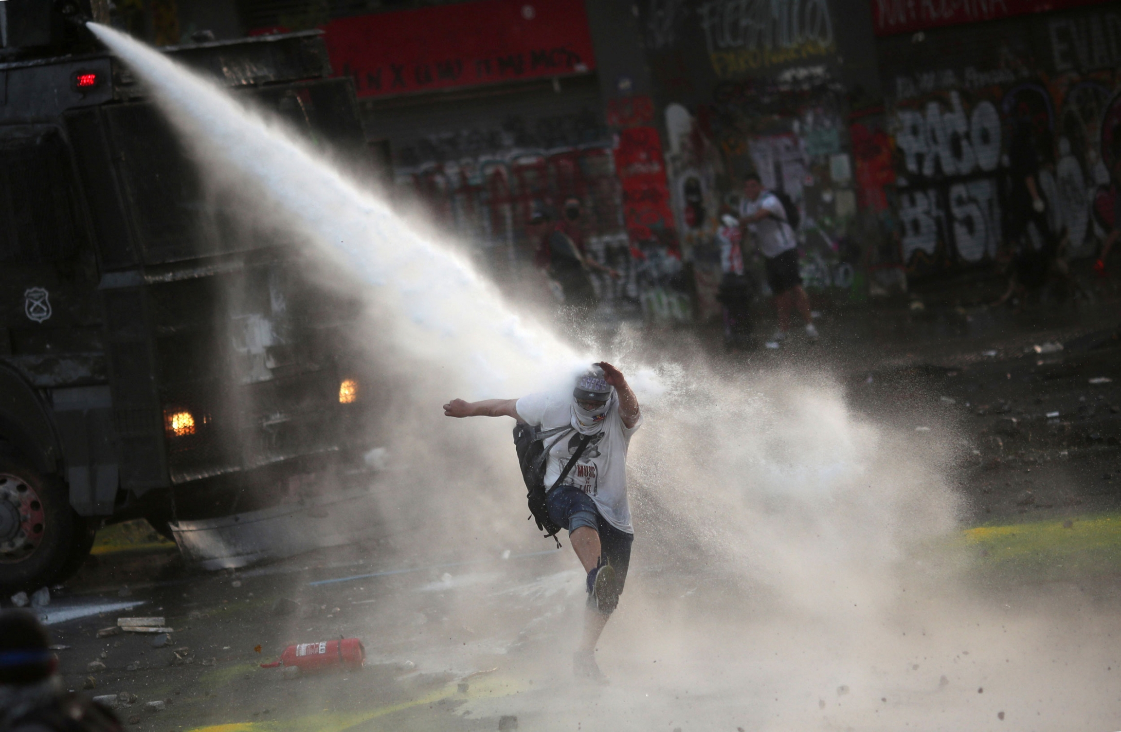 A person is shown being sprayed by a water cannon from above.