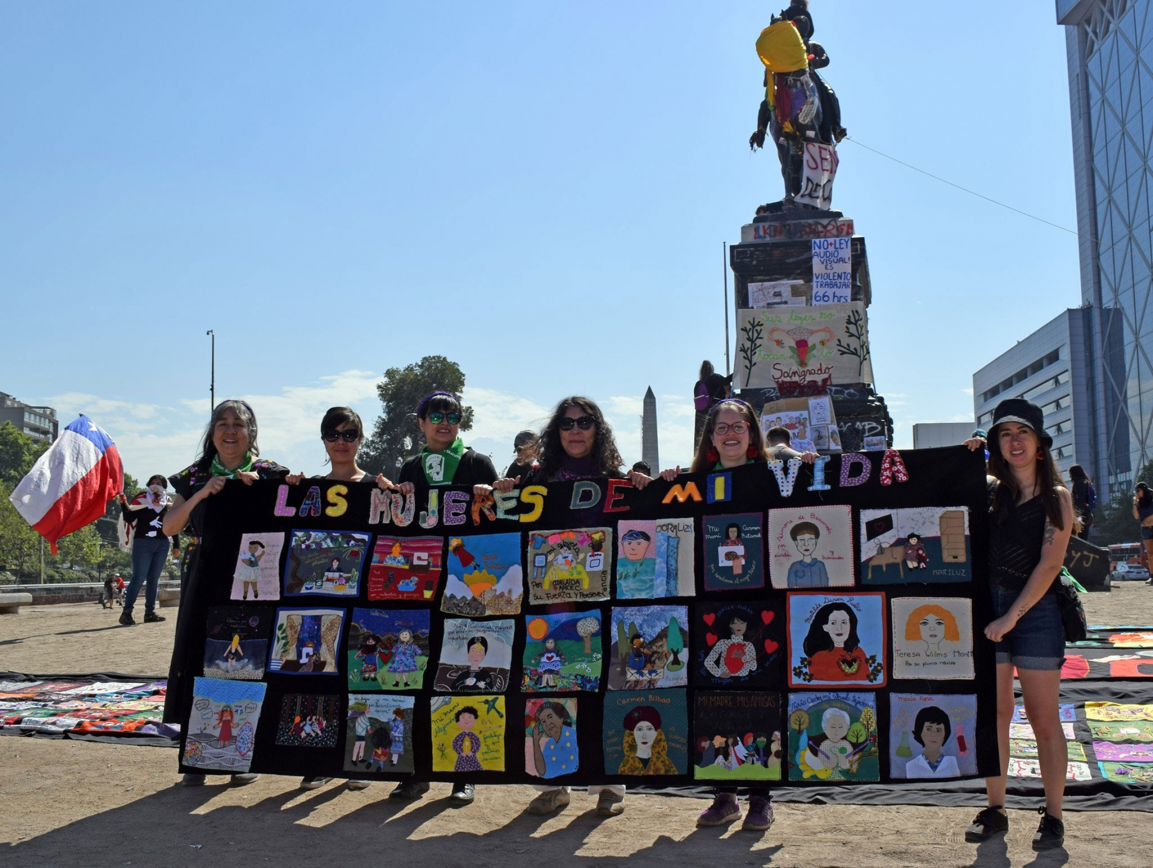 Several women are shown holding a tapestry with rows of embroidered blocks depicting slogans calling for legal abortion and an end to sexual assault.