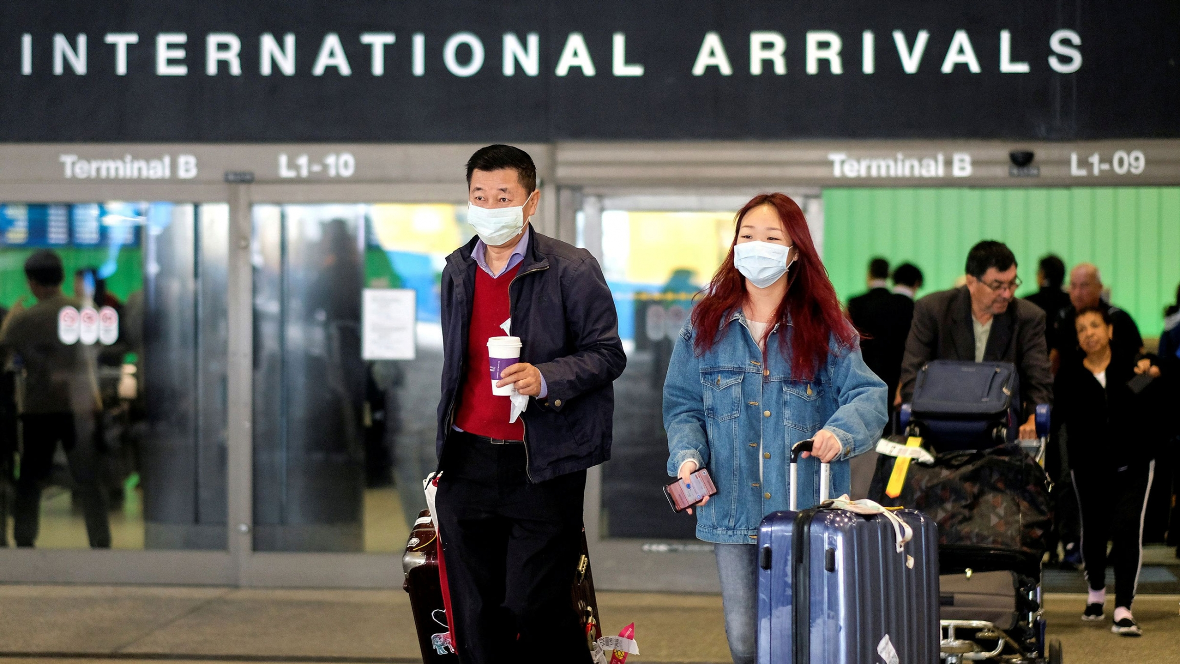 A man and a woman are shown with suitcases and wearing face masks while leaving the international arrivals terminal at Los Angeles International Airport.