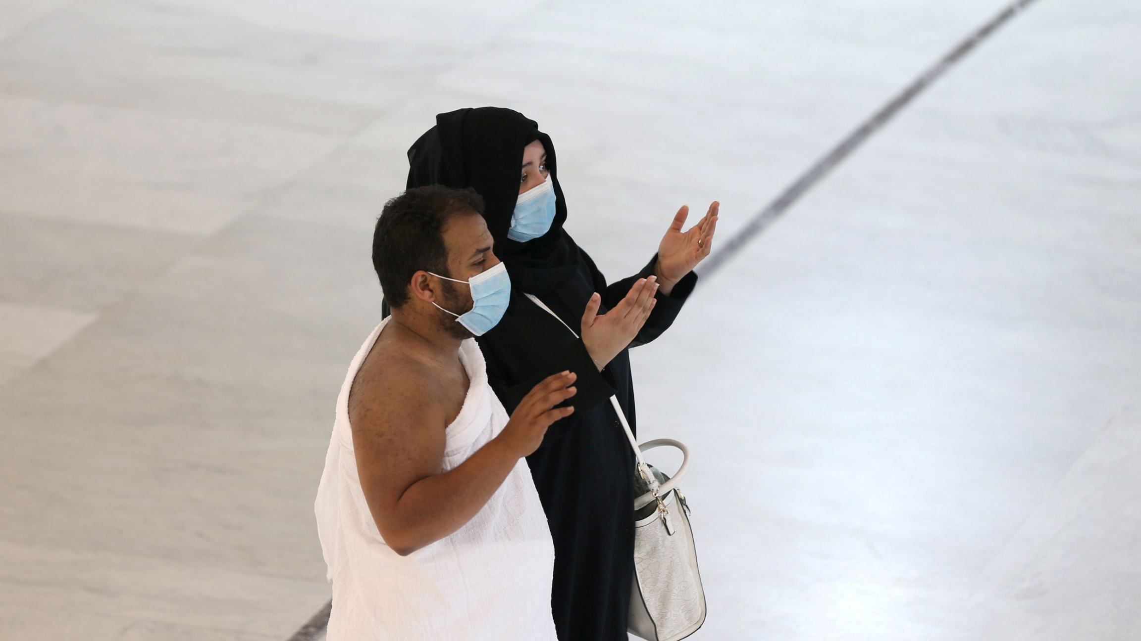 A man and woman are shown standing with their hands in the air and wearing face masks.