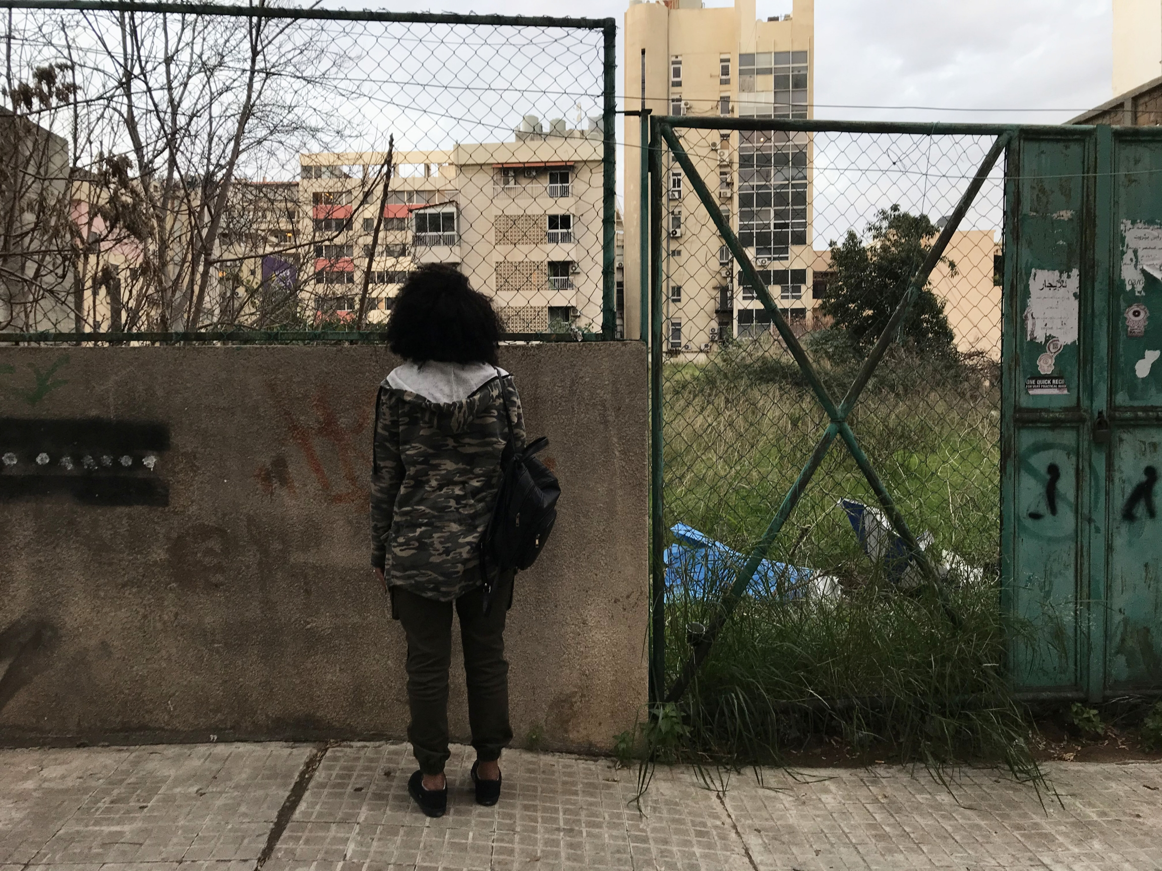 A young woman stands outside looking out at apartment buildings
