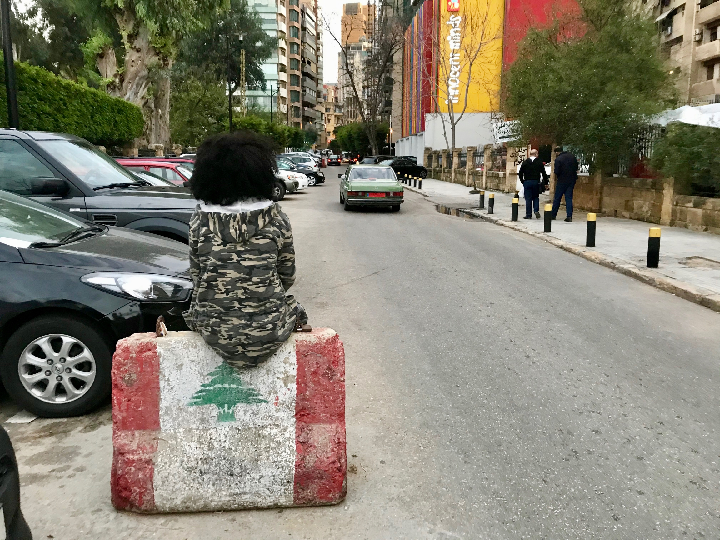 A young woman wearing a camouflage jacket sits on a barricade in middle of street.
