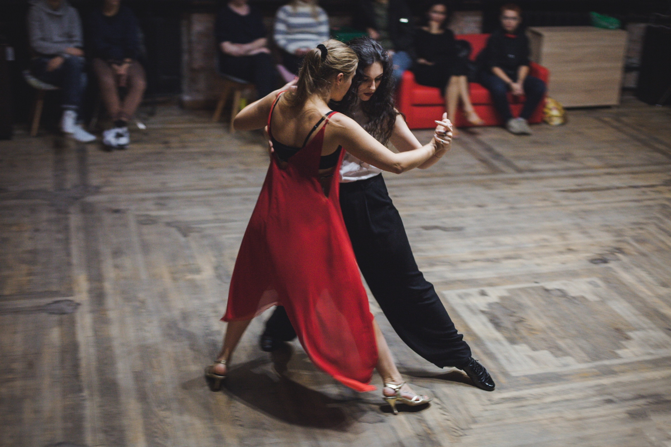 A woman in red dances with a woman in black at a dance studio