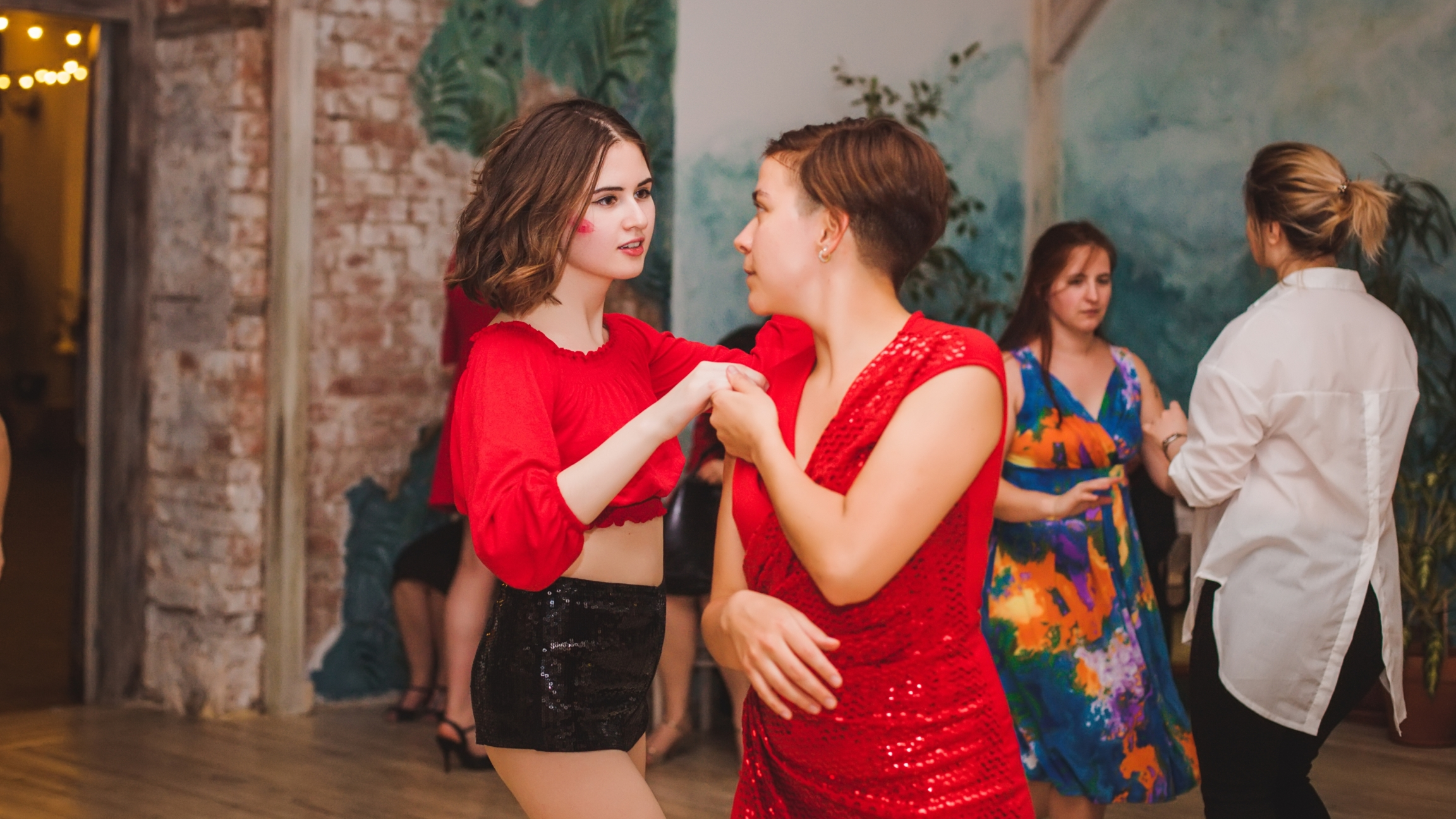 Two women dance together wearing red clothing.