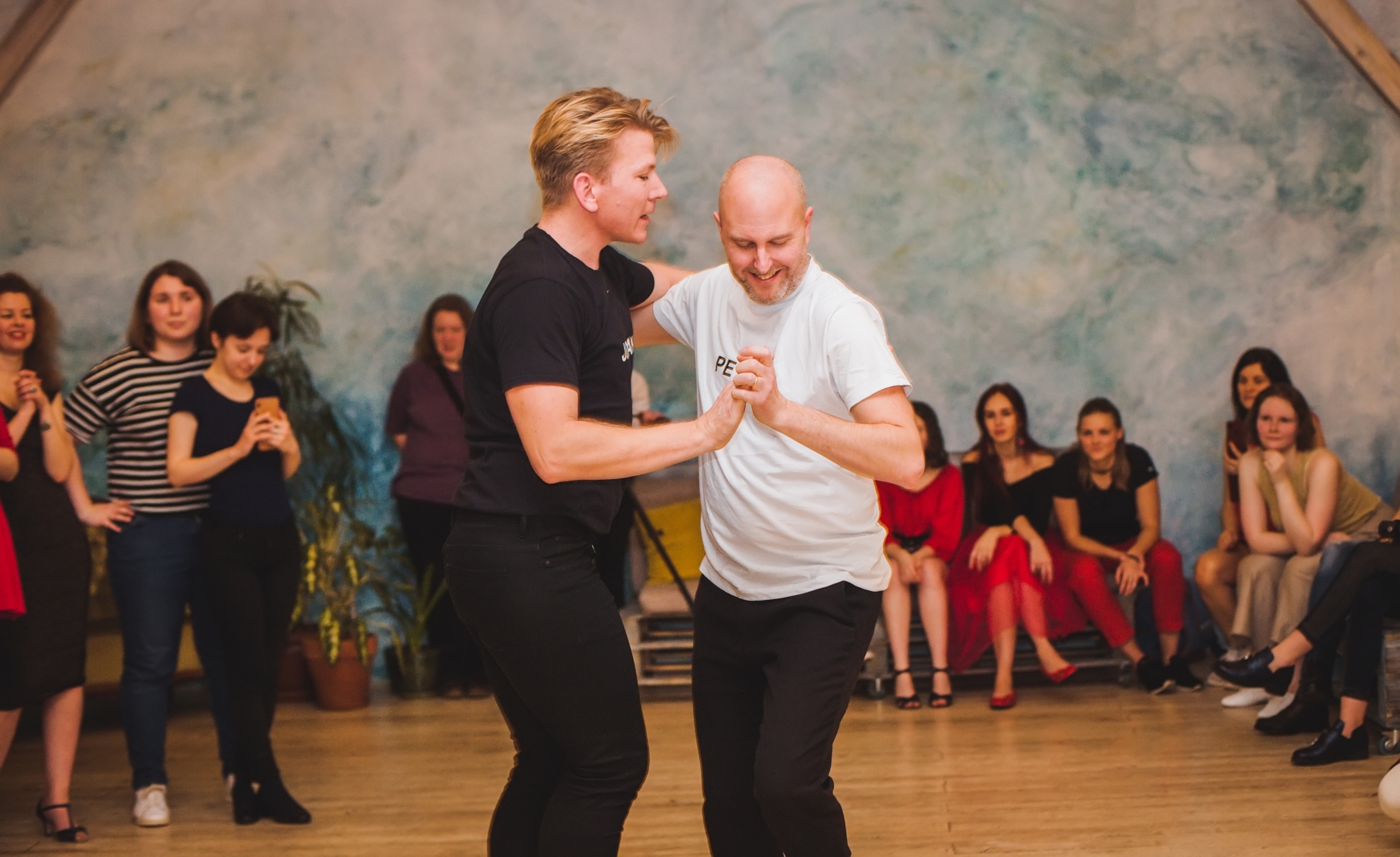 A salsa instructor dances with a student.
