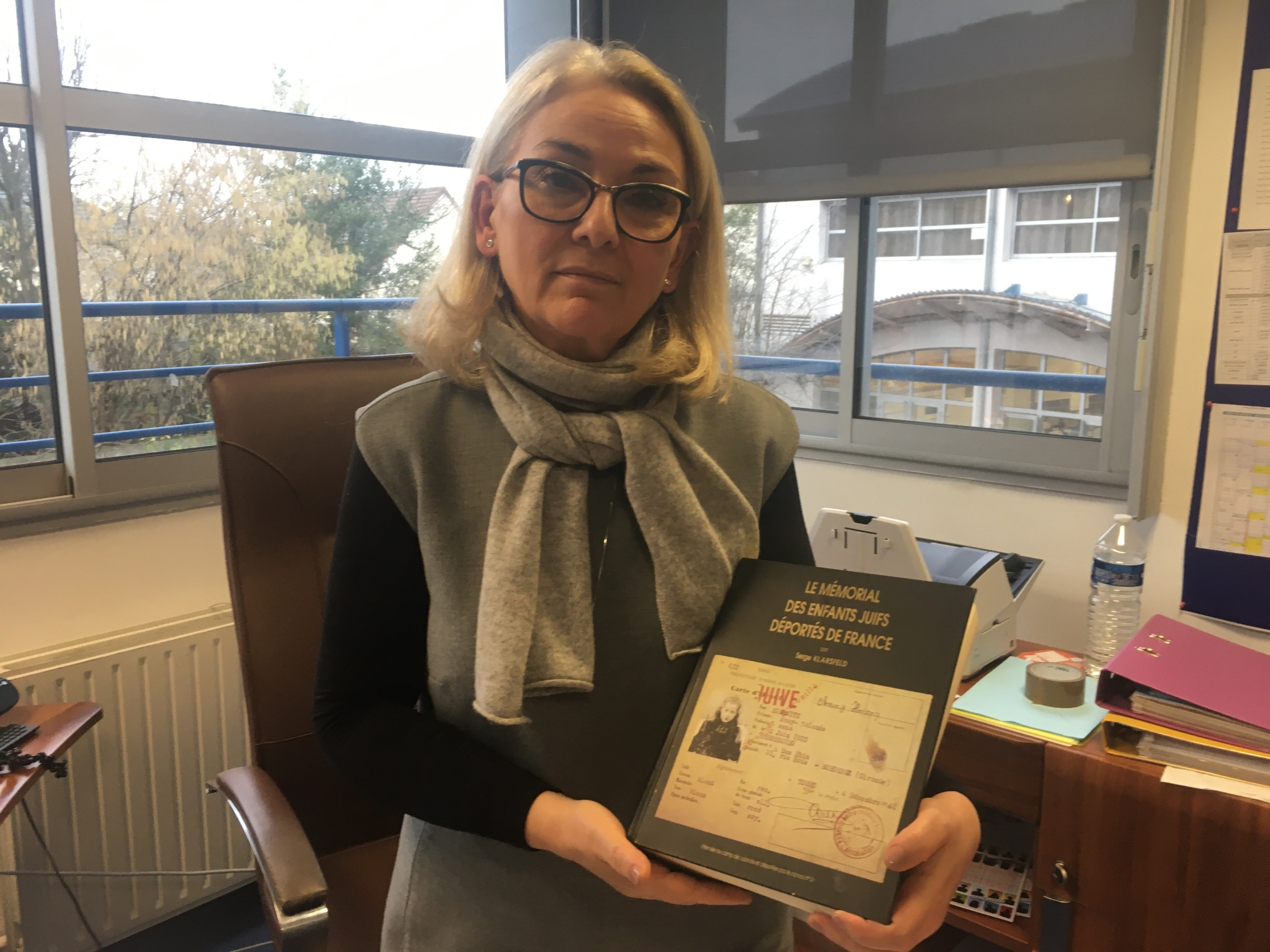 Sarah-Laure Attias, the director of a private Jewish school on the outskirts of Paris, holds a book listing the names of every Jewish child deported from France during World War II. Attias says students at her school need to be extra prepared when it come