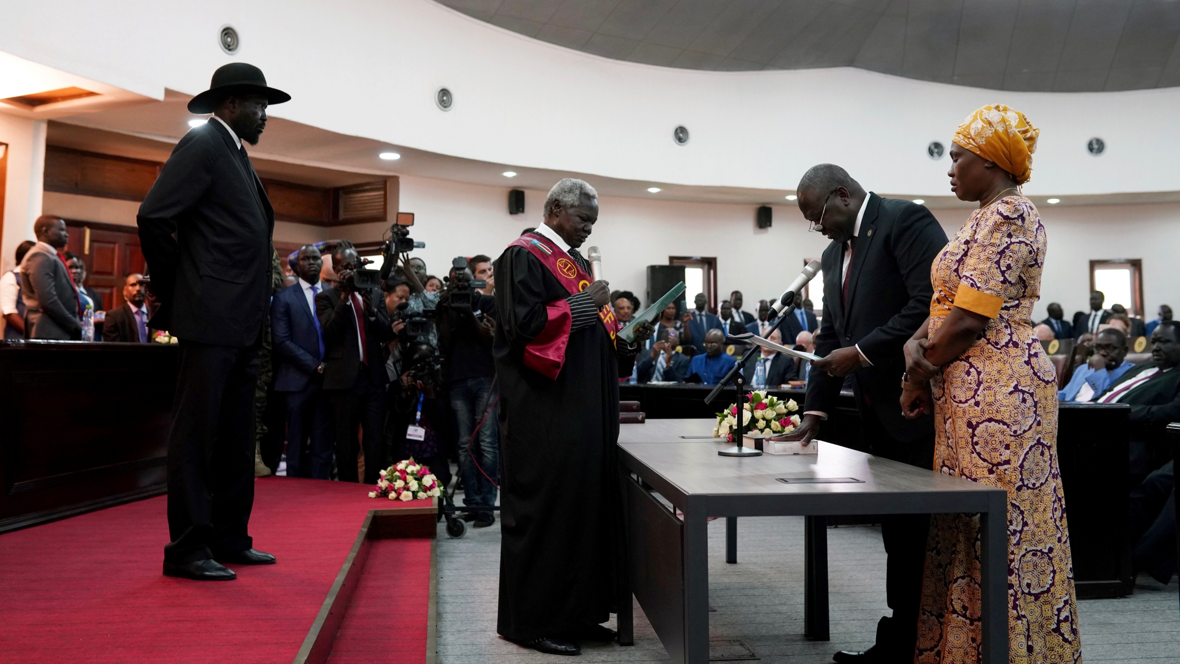 South Sudan's First Vice President Riek Machar takes the oath of office in front of President Salva Kiir and Chief Justice Chan Reech Madut at the State House in Juba, South Sudan, Feb. 22, 2020.