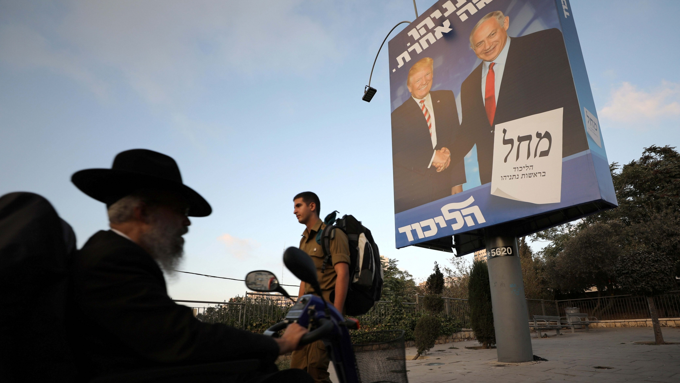 Ultra-Orthodox Jewish men walk past a Likud party election campaign banner depicting Israeli Prime Minister Benjamin Netanyahu and U.S. President Donald Trump in Jerusalem September 11, 2019.