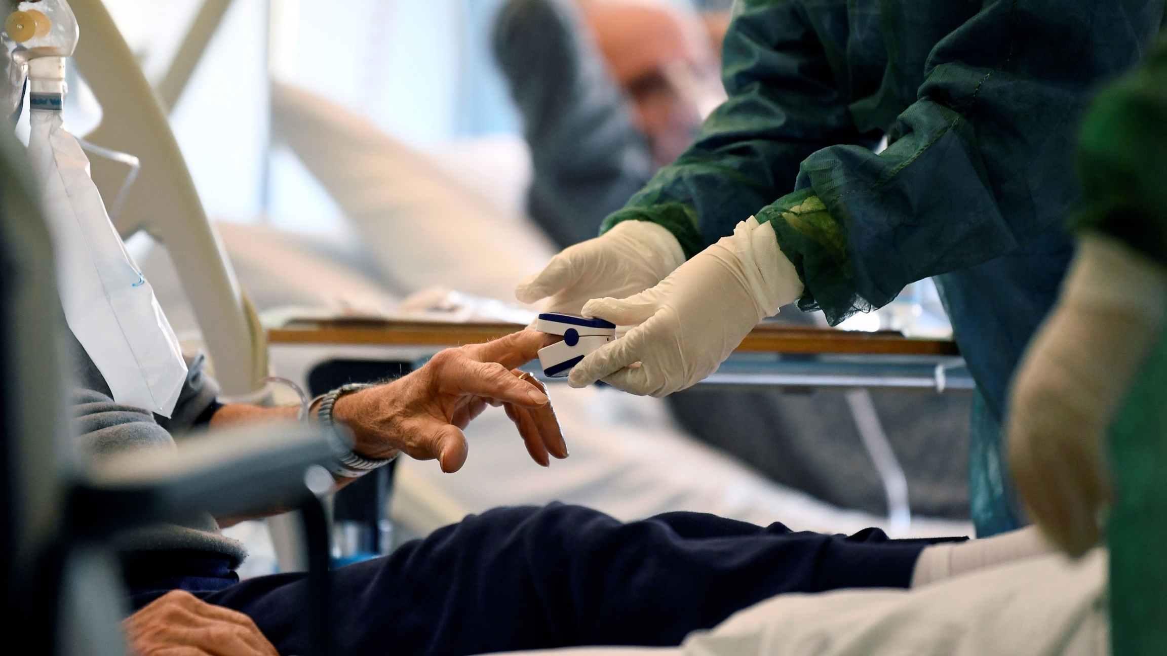 The hands of a medical professional are shown wearing protective gloves and putting a device on a patient's finger.