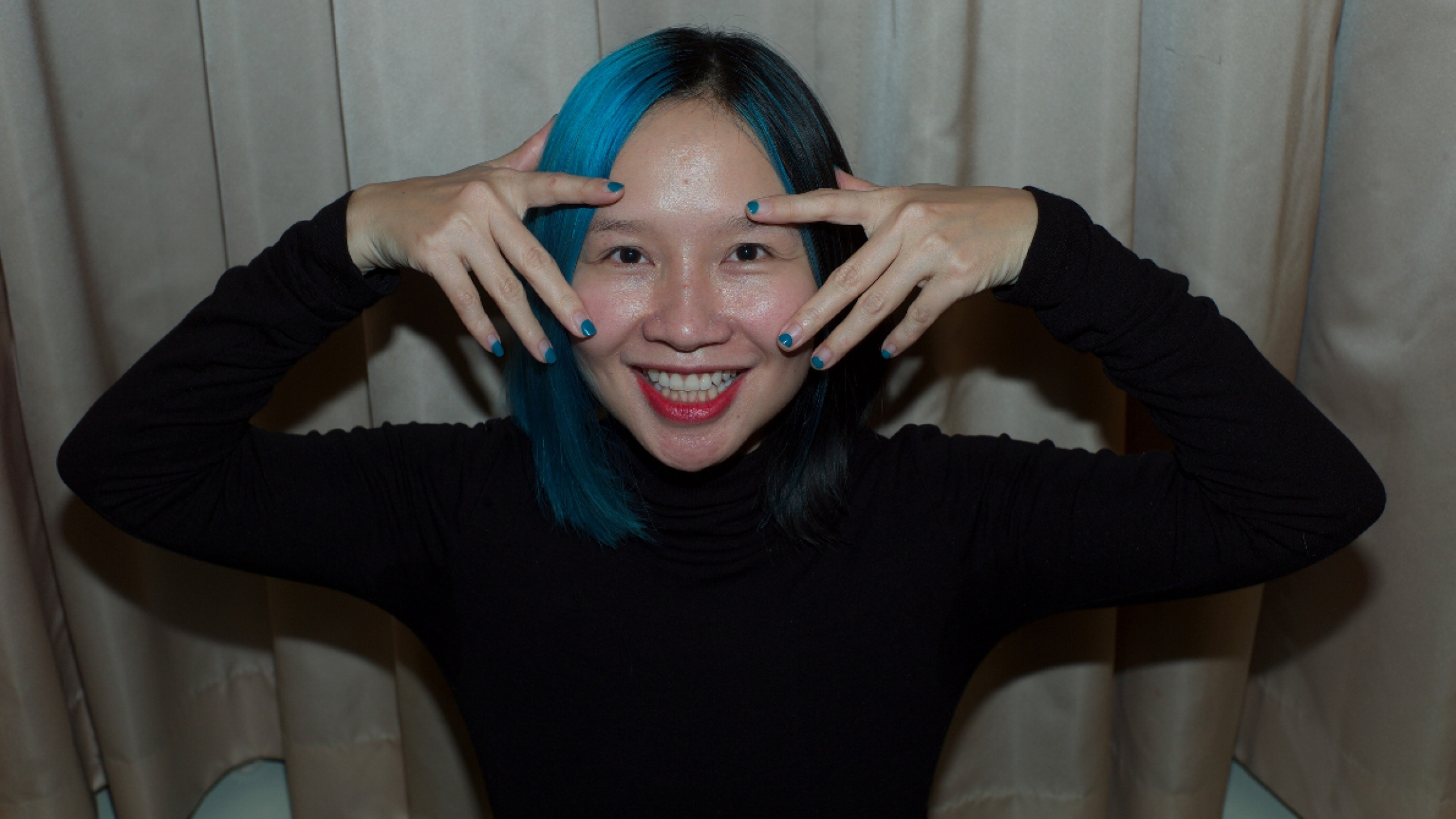 A voman with her hair painted blue holds both or her hands by her eyes.