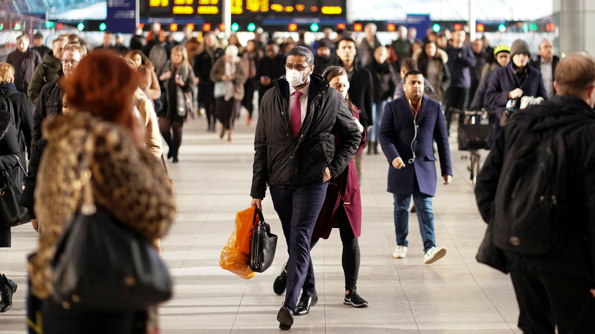 A large crowd of people are seen at Waterloo station with a man in the center of the frame wearing a face mask.