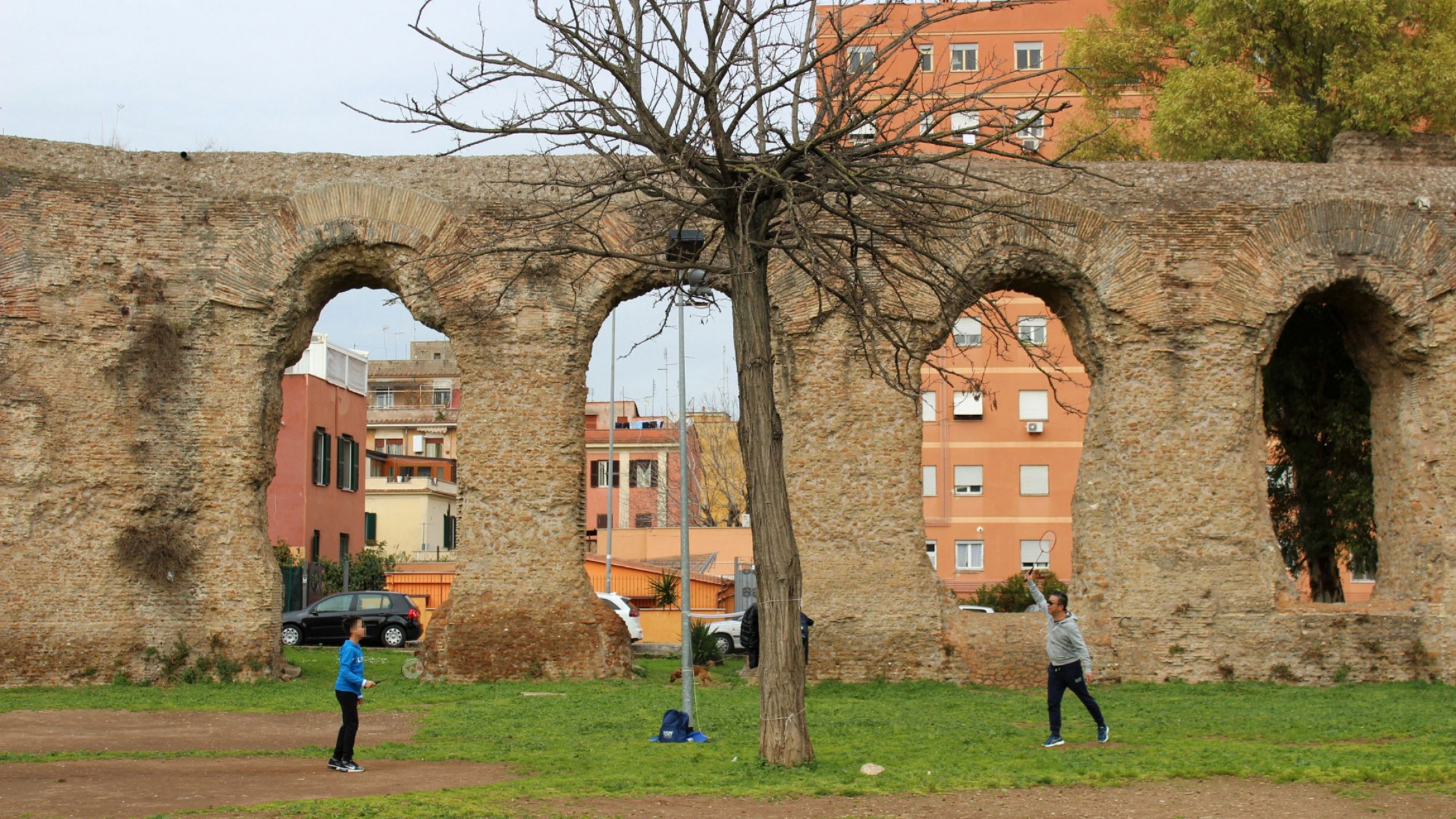 A man and a boy play badminton in front of ruins in a park