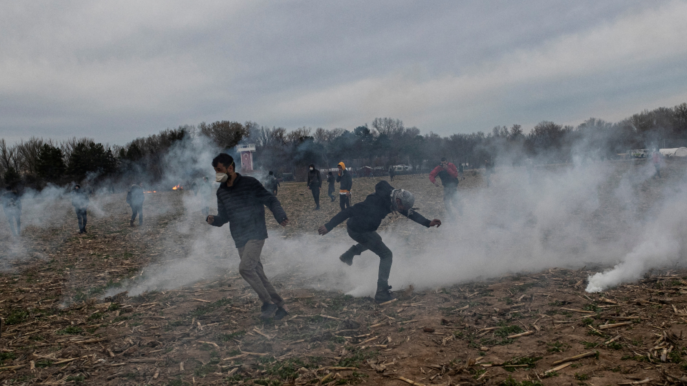 Several men run in a field while teargas is in the air.