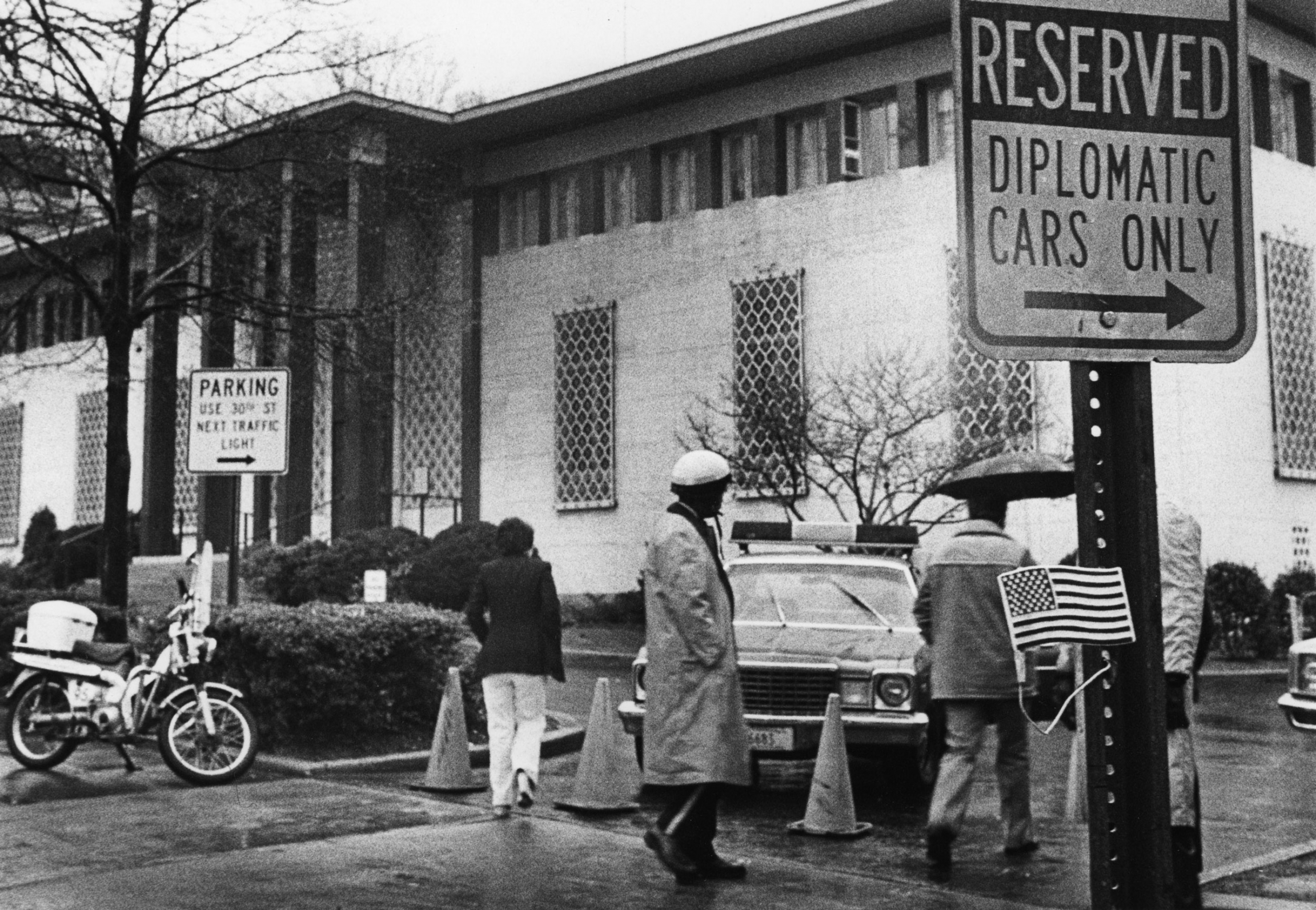 Several people and a police car are shown in this black and white photograph with the former Embassy of Iran in the background.