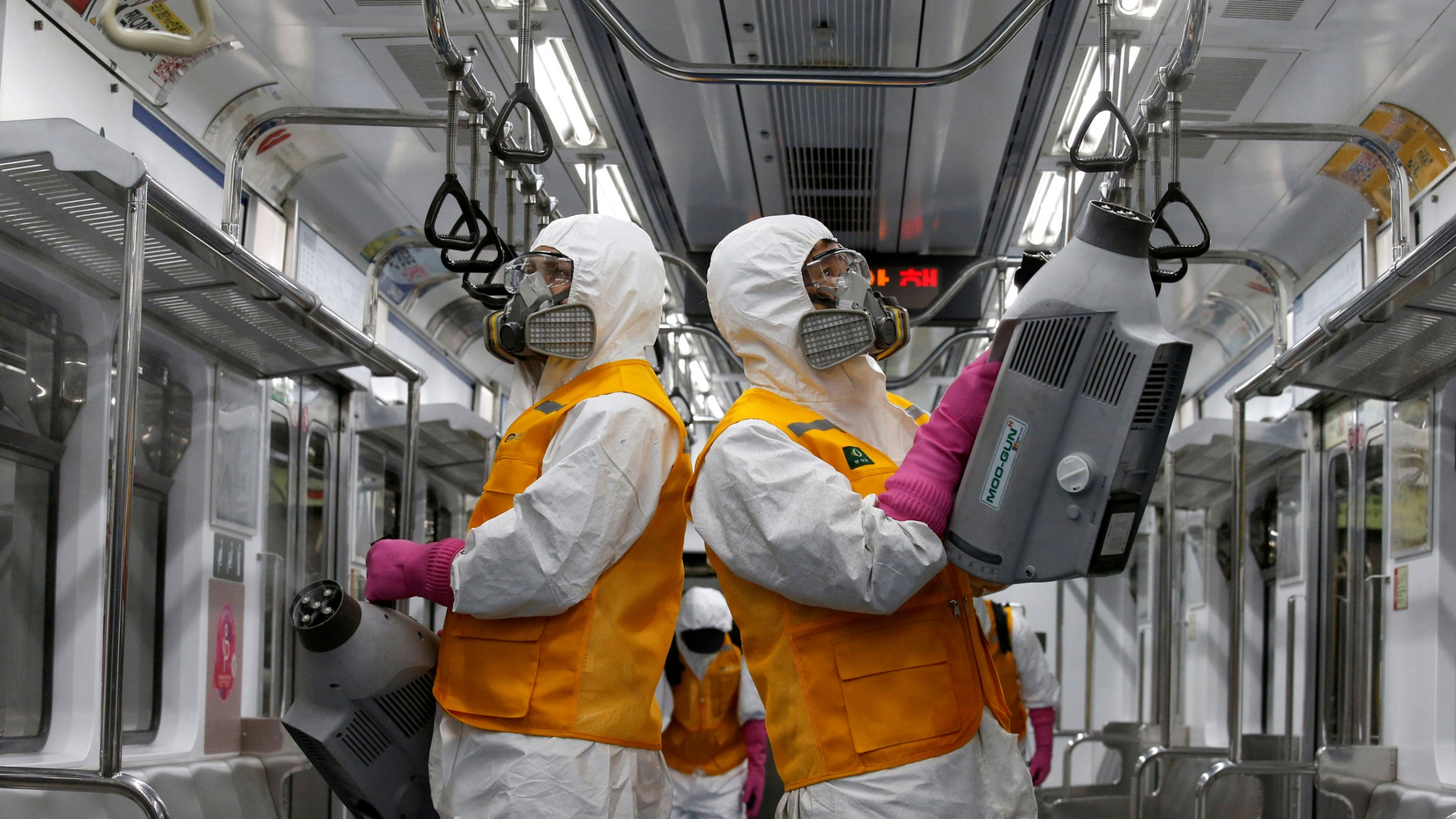 Two workers are shown inside a subway car with white and orange protective and carrying machines that are cleaning the car.