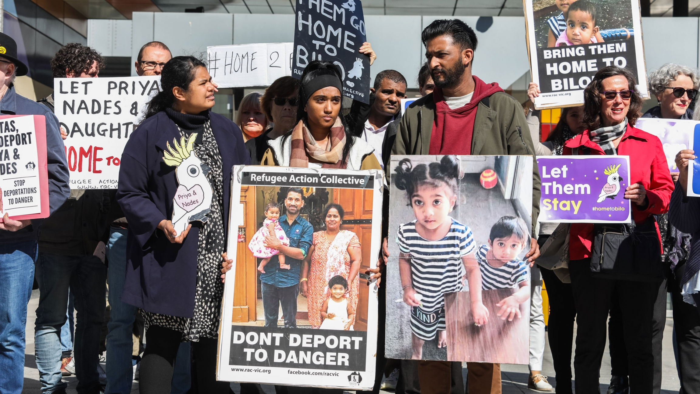 A group of protesters are shown holding placards with pictures of a Tamil family that includes the father, mother and their two small children.