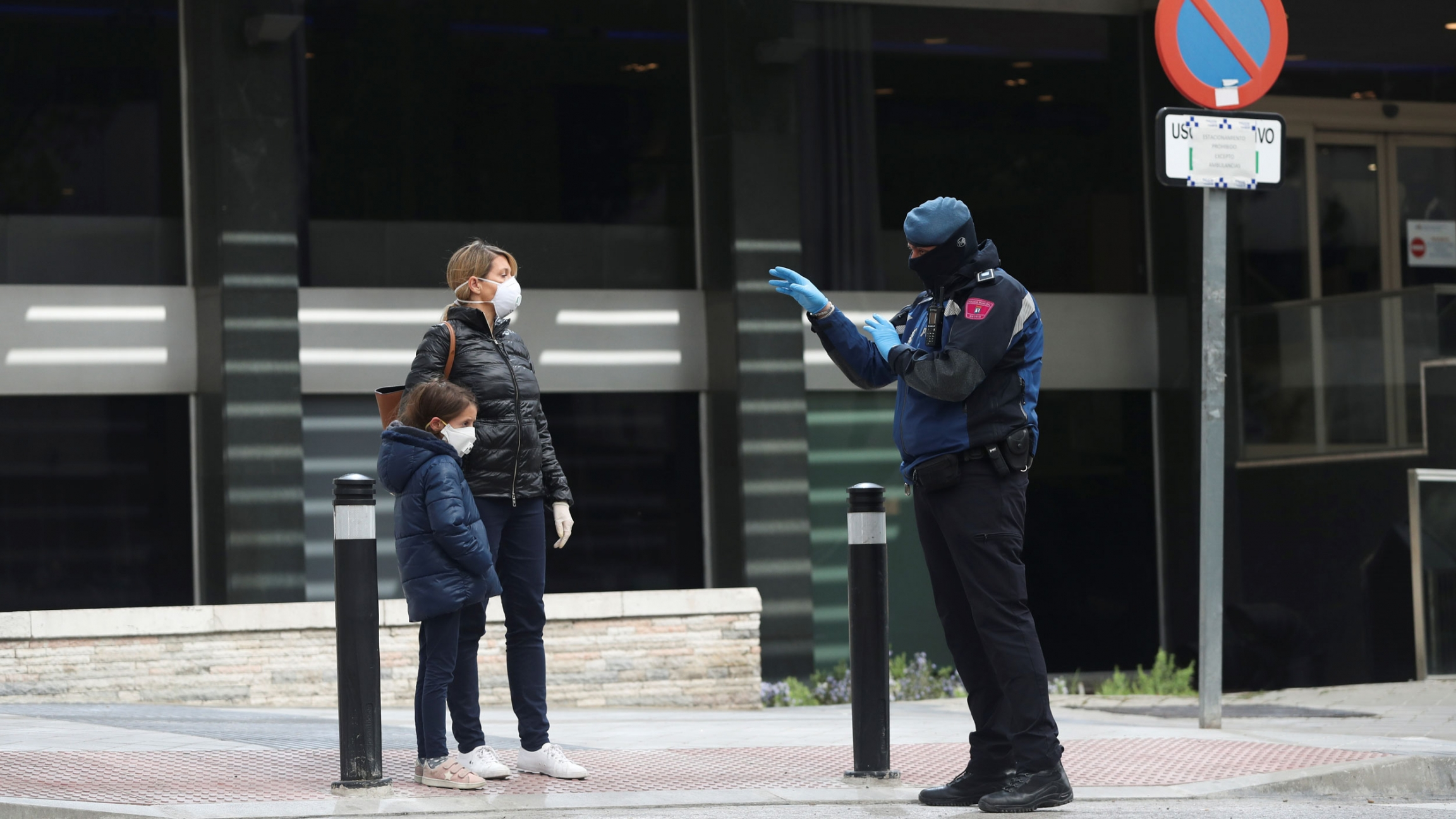 A police officer talks to a woman and child, all in face masks, outside a hotel