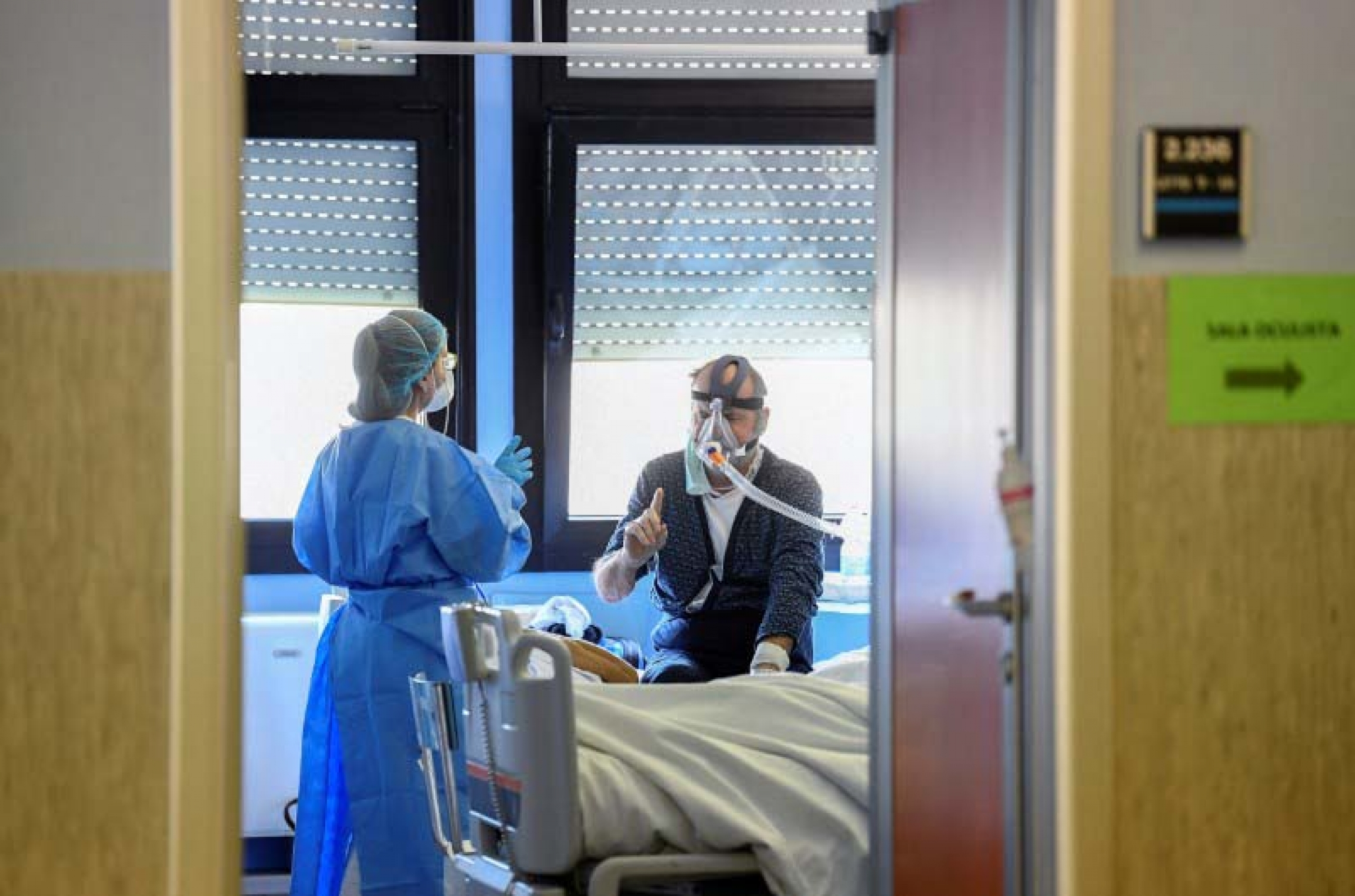 A medical worker wearing a protective mask and suit speaks with a patient suffering from coronavirus disease (COVID-19) in an intensive care unit at the Oglio Po hospital in Cremona, Italy March 19, 2020.