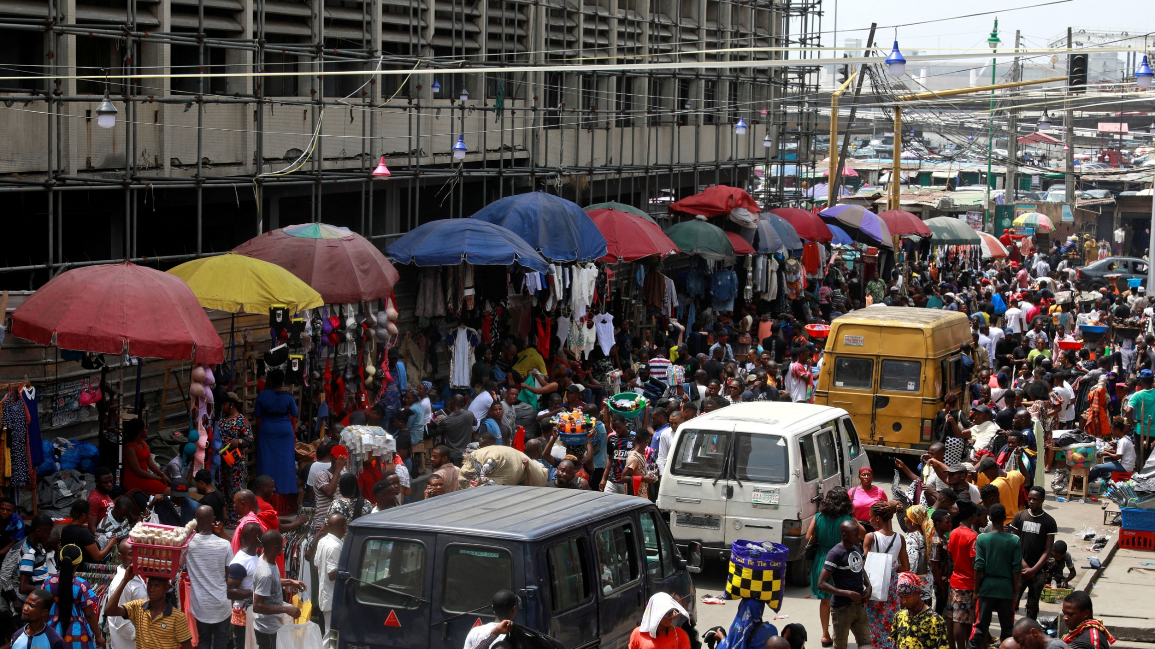 A bustling market is shown with hundreds of peope packed into the street lined with large vendor umbrellas.
