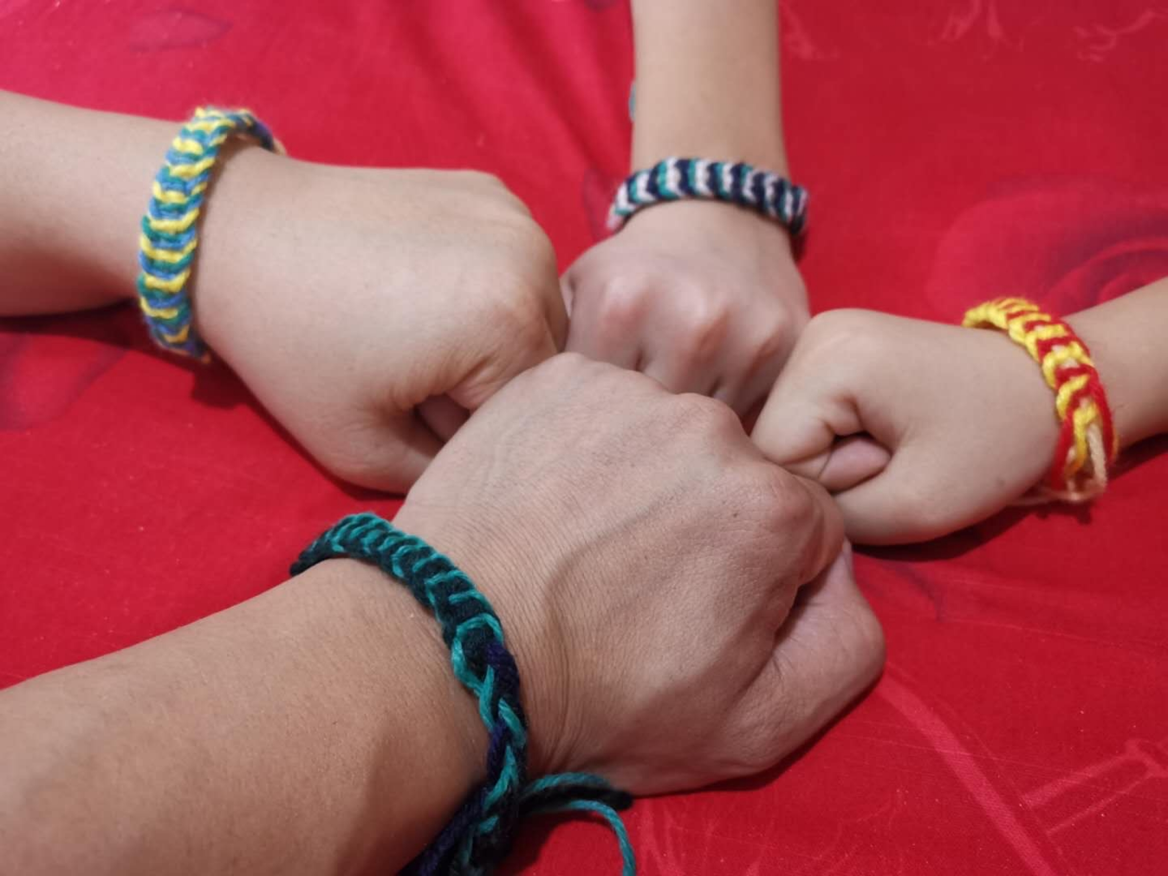 Four arms fist bump to show off their bracelets on their wrists.