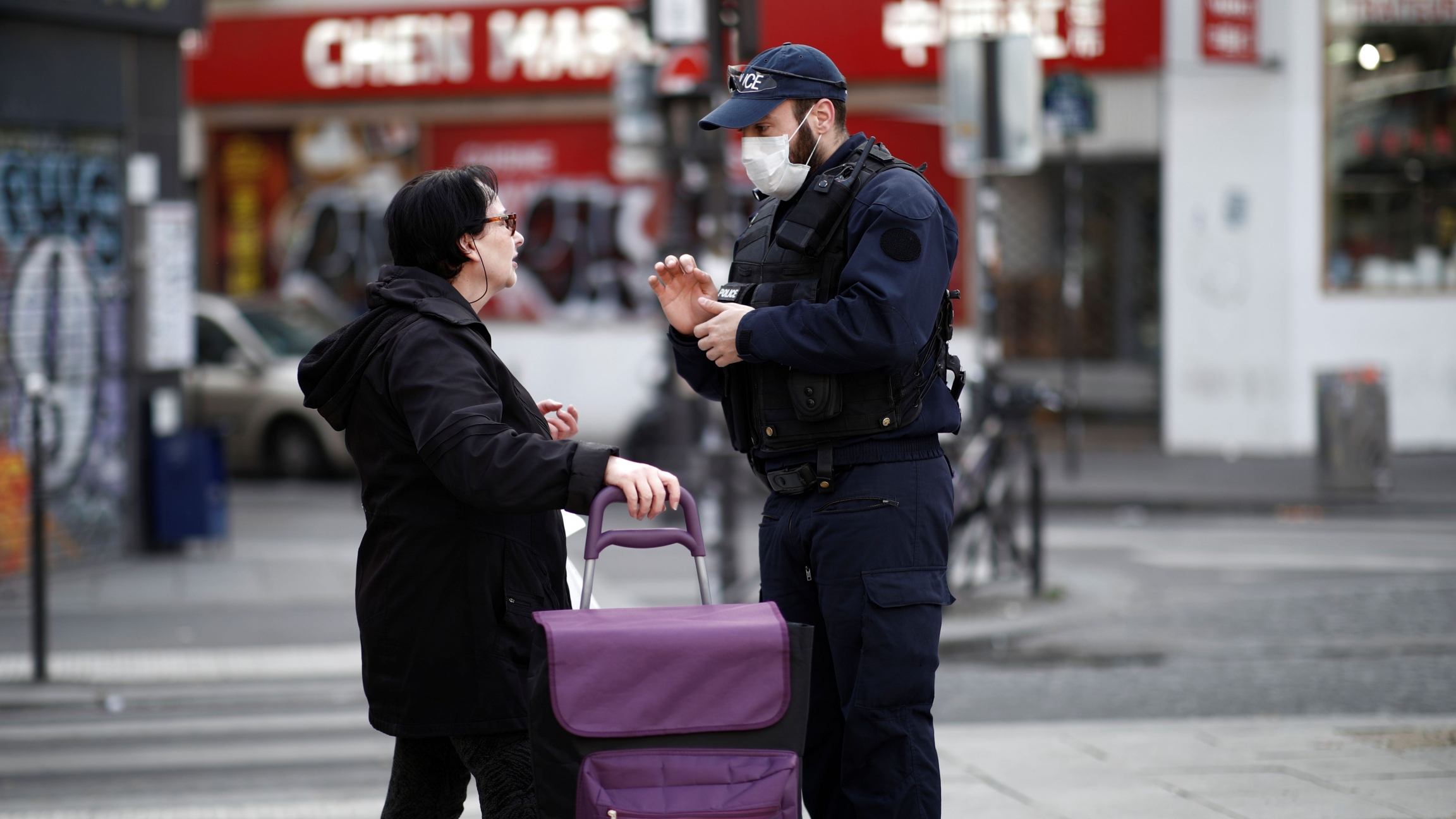 A French police officer controls a bystander in Belleville neighborhood as a lockdown imposed to slow the rate of the coronavirus disease (COVID-19) contagion started midday March 17.