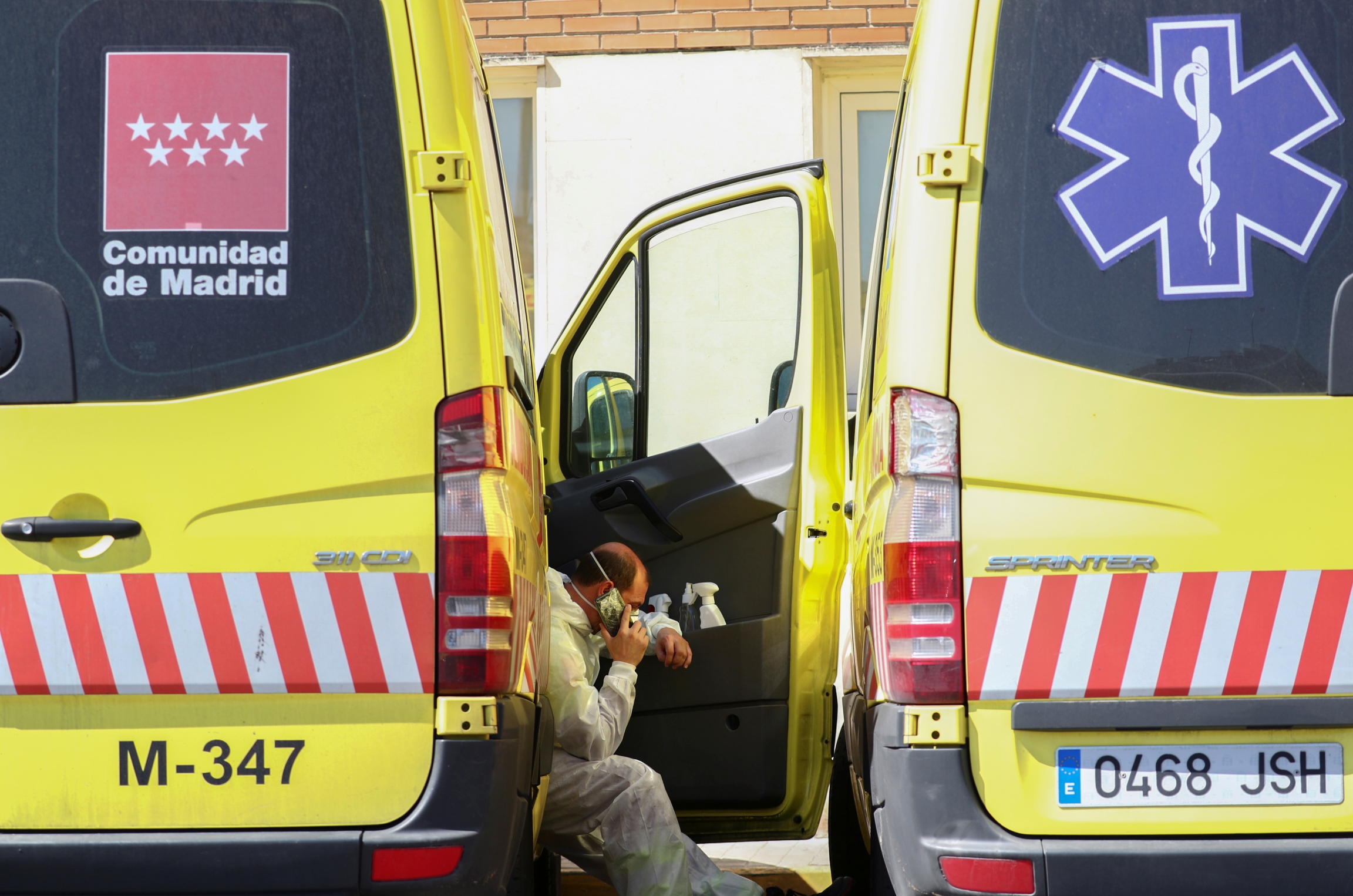 An ambulance driver rests between two vehicles and talks on the phone