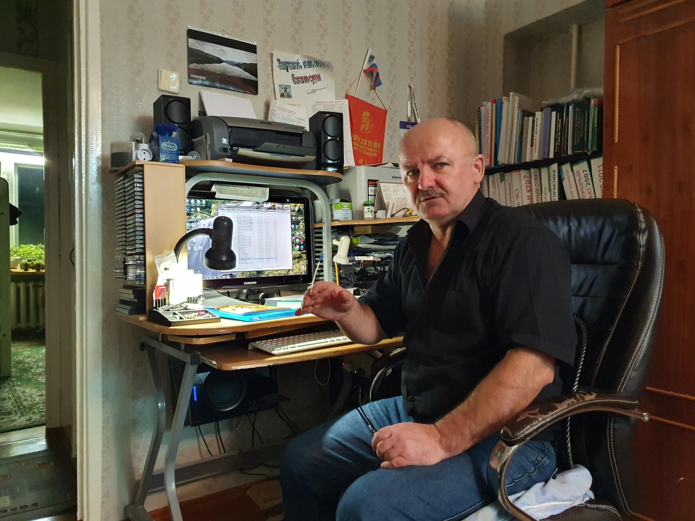 A bald man sits at a desk