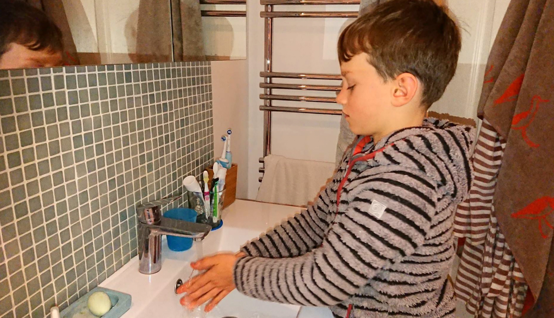Jacob Gortmans demonstrates the proper 20-second hand-washing duration at his home in London.