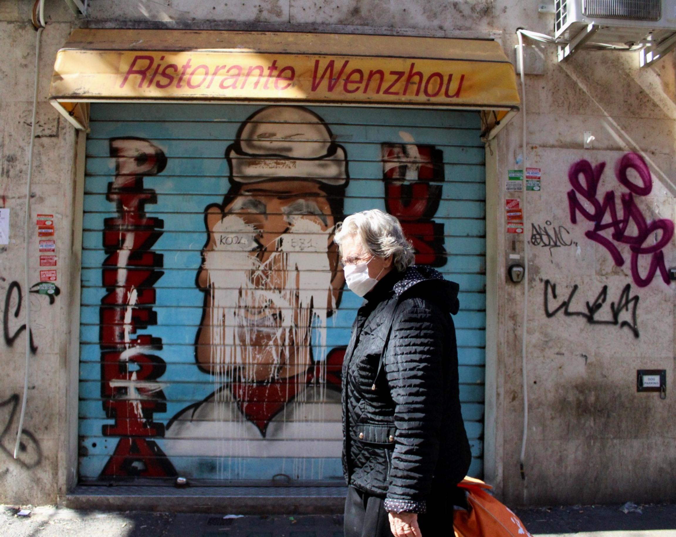 A woman wearing a mask walks by a popular Chinese restaurant inTorpignattara, Italy.