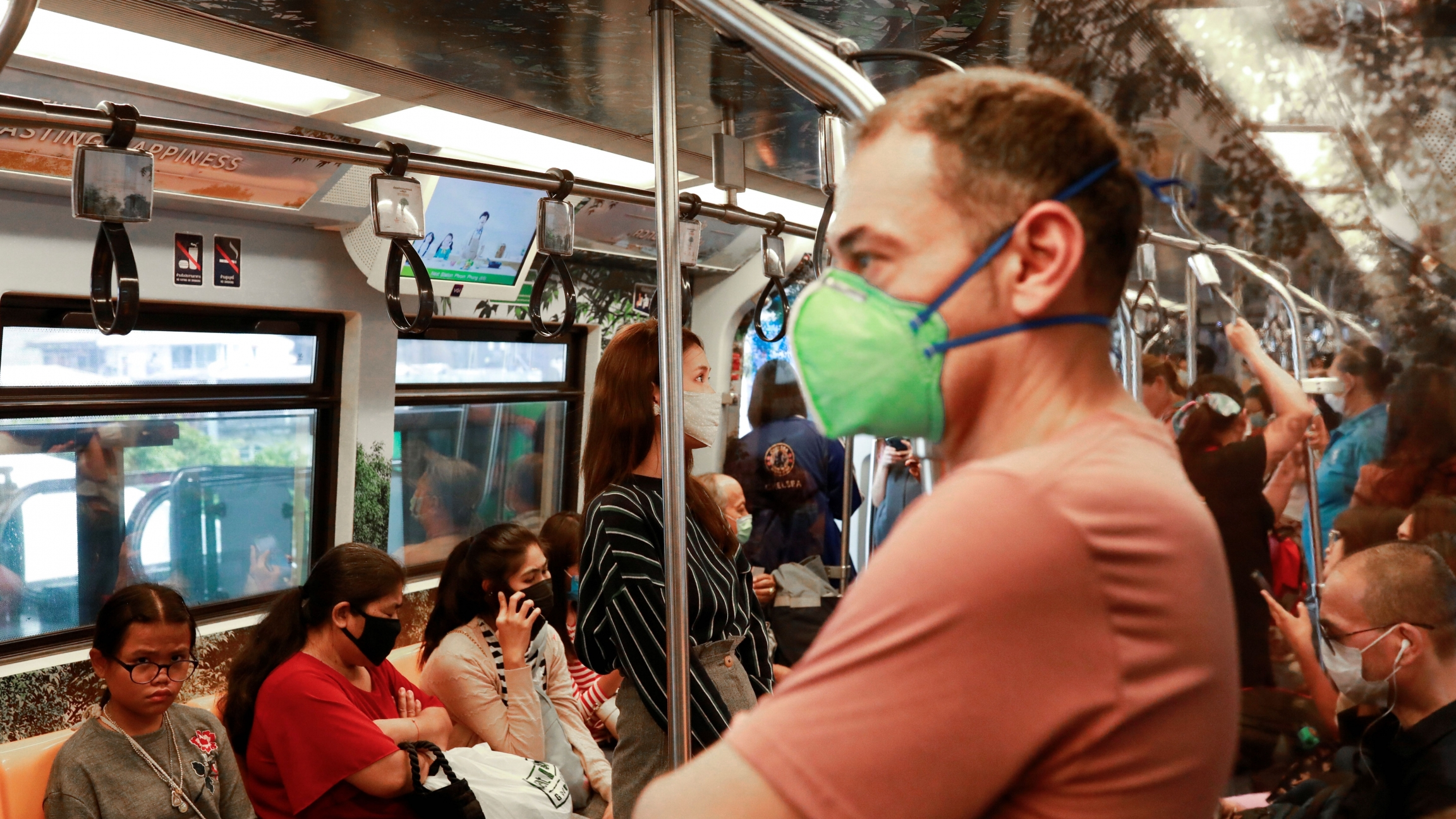 Passengers wear protective masks due to the coronavirus outbreak on a train in Bangkok, March 16, 2020.