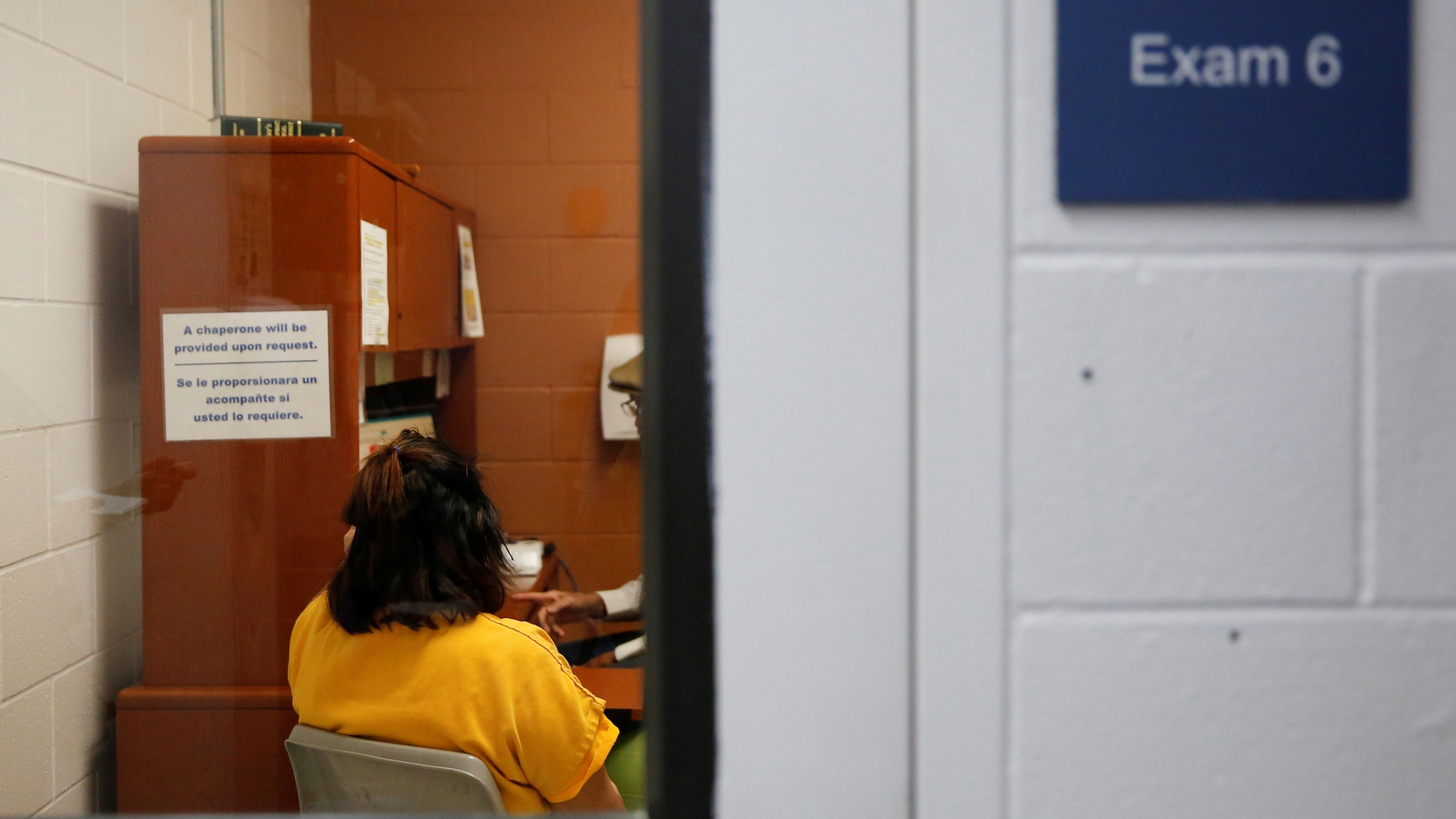 A detainee talks with an employee in an exam room in the medial unit during a media tour at Northwest ICE Processing Center, one of 31 dedicated ICE facilities that house immigration detainees, in Tacoma, Washington, Dec. 16, 2019.
