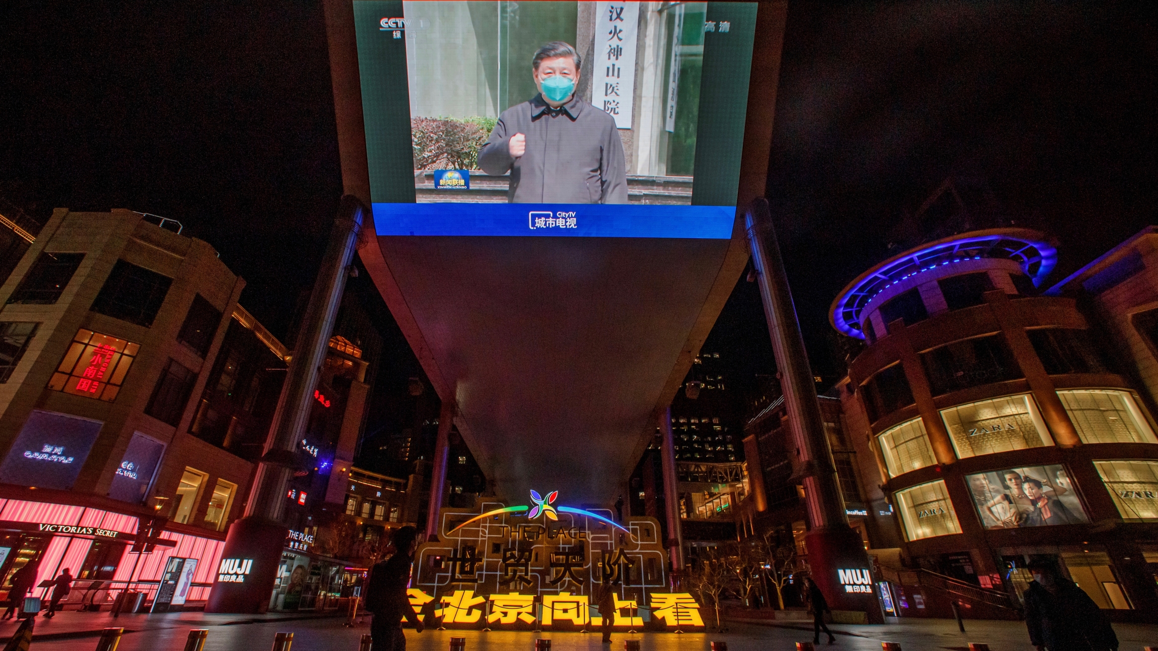 A screen shows a CCTV state media broadcast of Chinese President Xi Jinping's visit to Wuhan at a shopping centre in Beijing as the country is hit by the outbreak of the novel coronavirus, China, March 10, 2020.