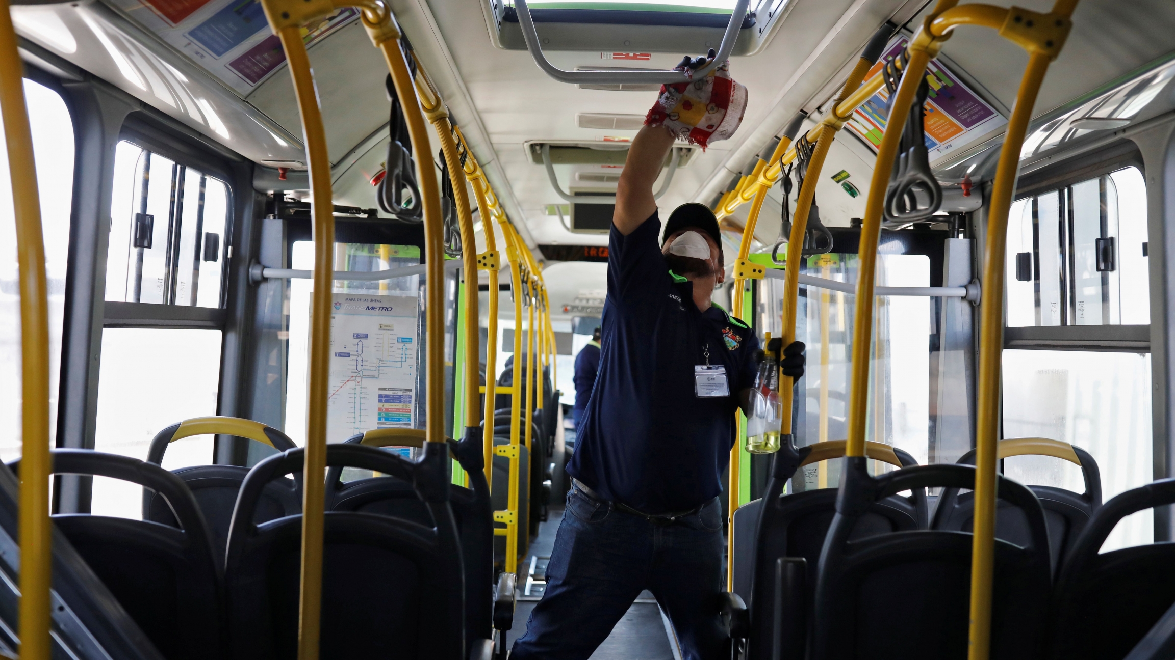 A worker wears a protective face mask works while cleaning the interior of a public bus, amid concerns over the spread of coronavirus disease (COVID-19), in Guatemala City, Guatemala, March 15, 2020.