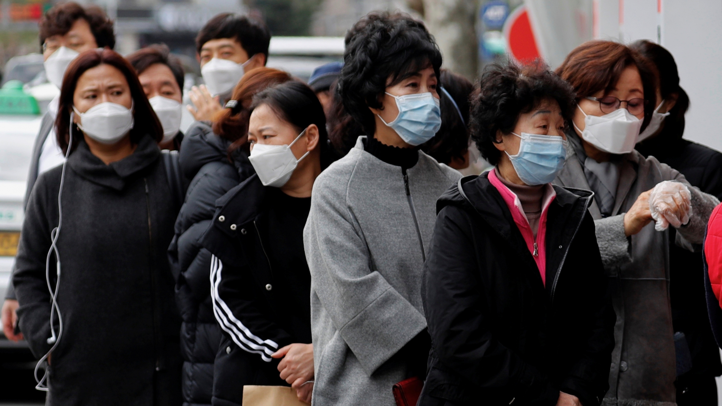 People wearing masks stand in a line to buy face masks in front of a drug store amid the rise in confirmed cases of the novel coronavirus disease of COVID-19 in Daegu, South Korea, March 3, 2020.