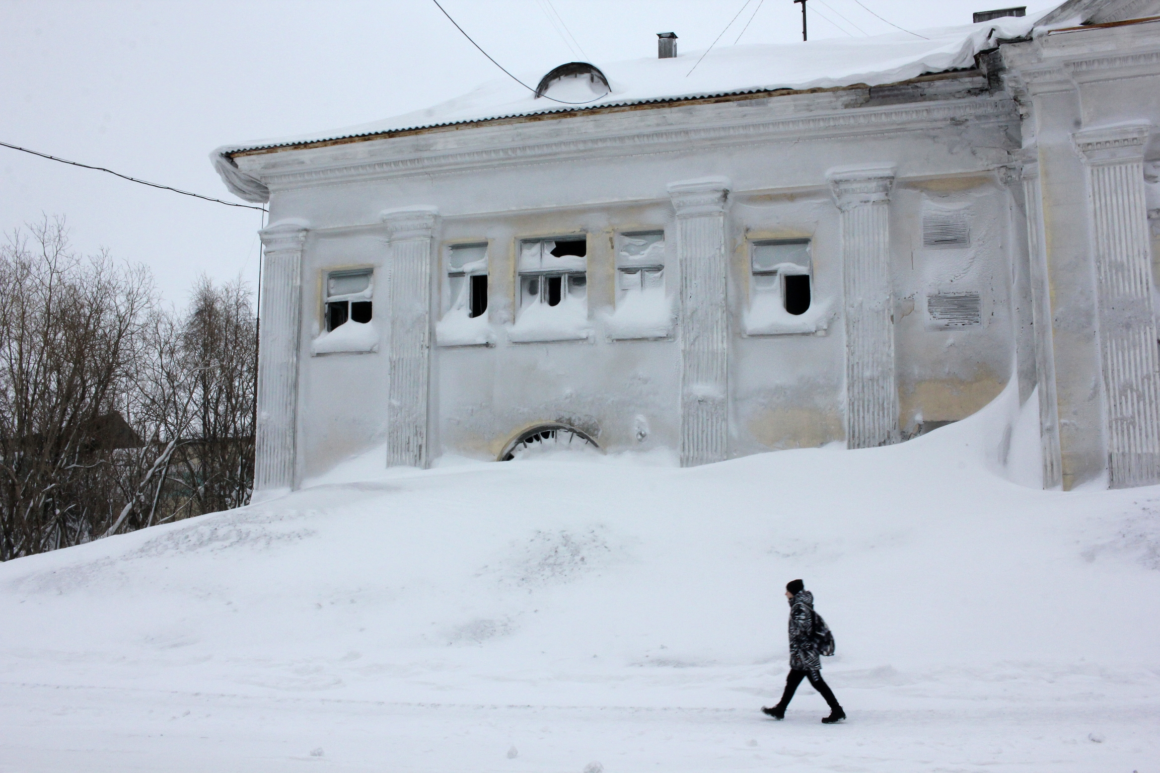 A man walks past an abandoned building in the snow