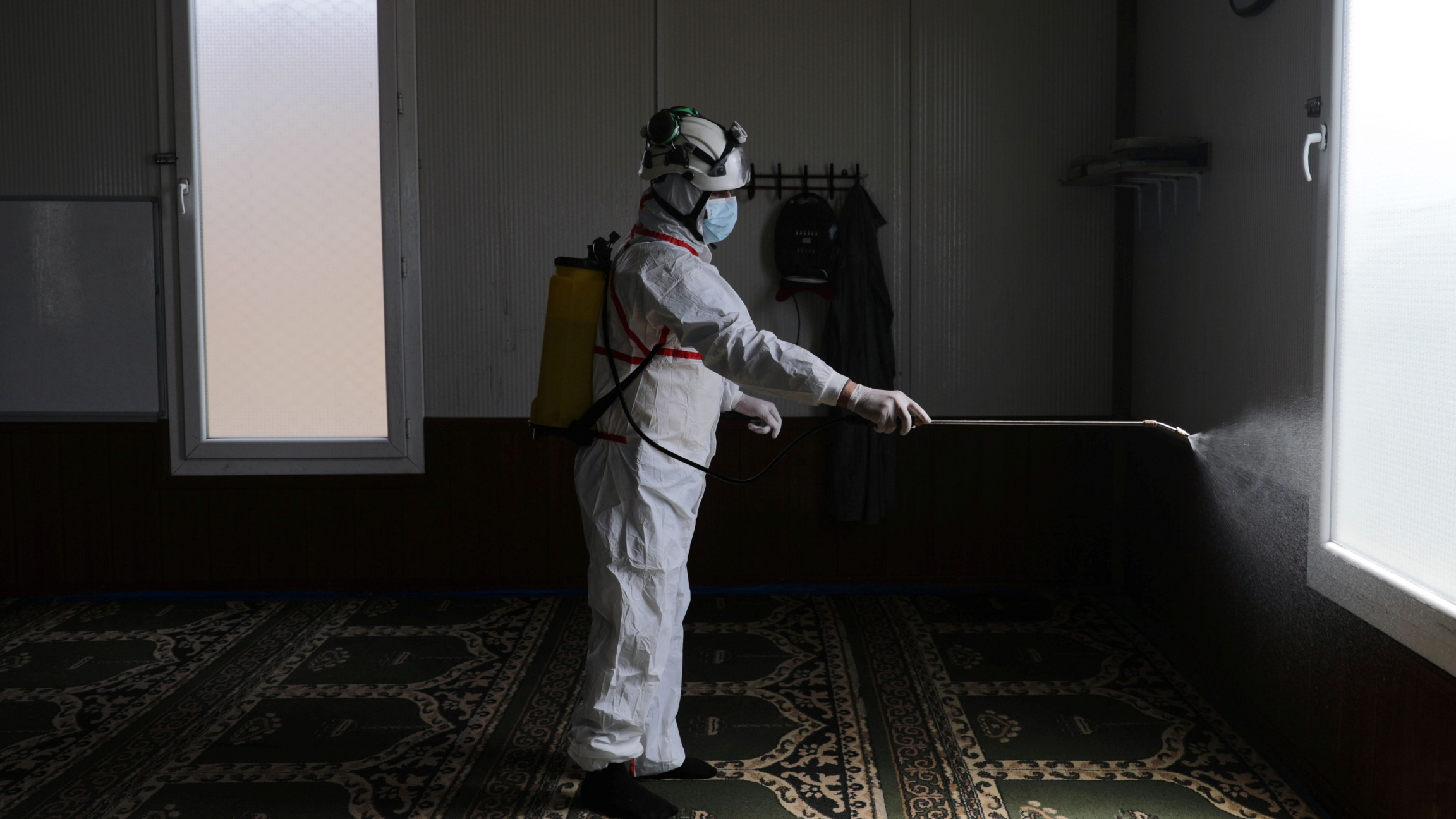 A member of the Syrian Civil Defense sanitizes inside the mosque at the Bab al-Nour internally displaced persons camp, to prevent the spread of the coronavirus disease (COVID-19) in Azaz, Syria, March 26, 2020.