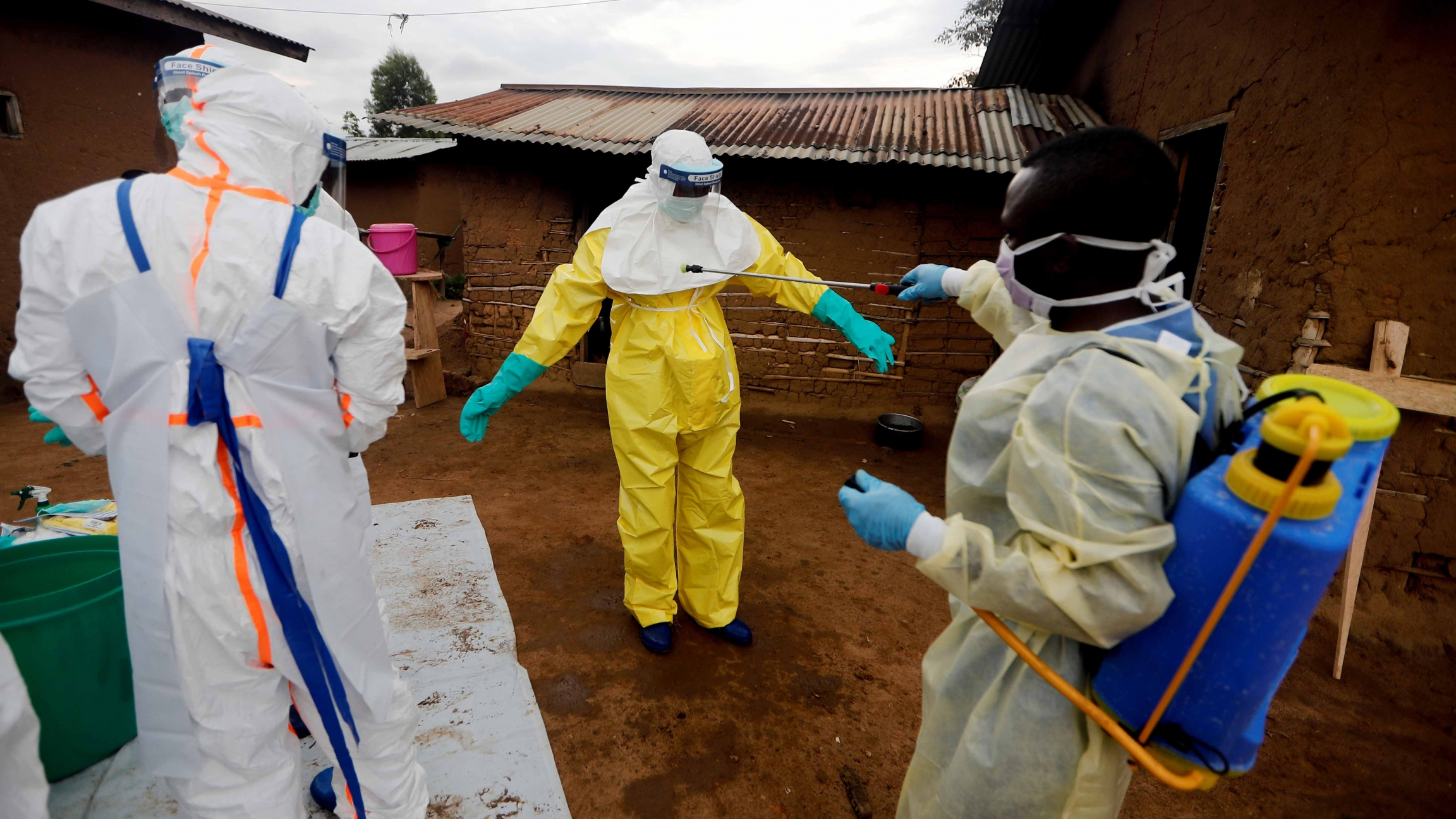 A health care worker who volunteered in the Ebola response, decontaminates his colleague after he entered the house of a woman suspected of dying of Ebola, in the eastern Congolese town of Beni in the Democratic Republic of the Congo, October 2019.