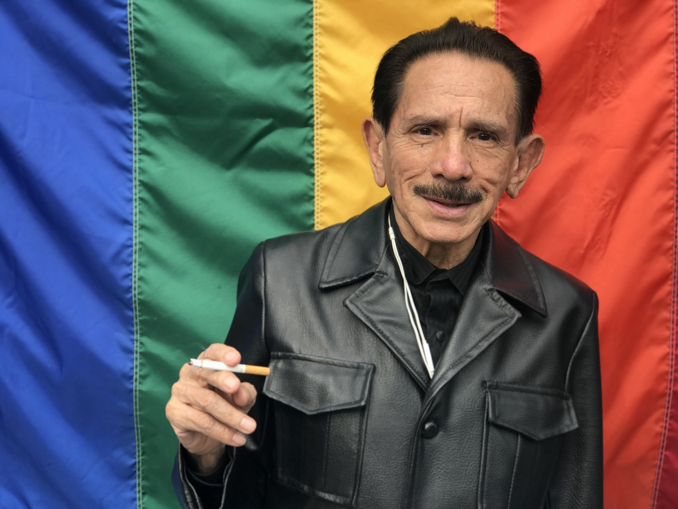 A man wearing a leather vest smokes in front of rainbow flag