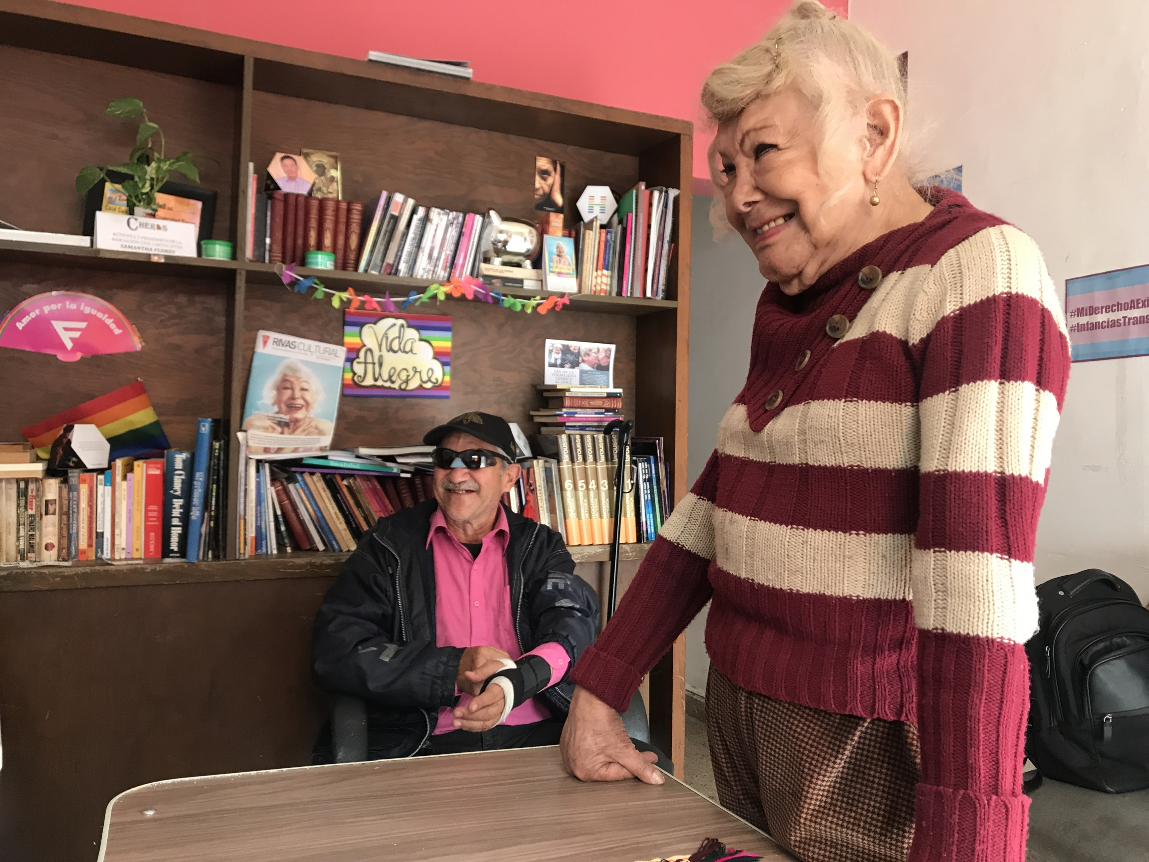 A woman talks with friends in a center near a bookshelf