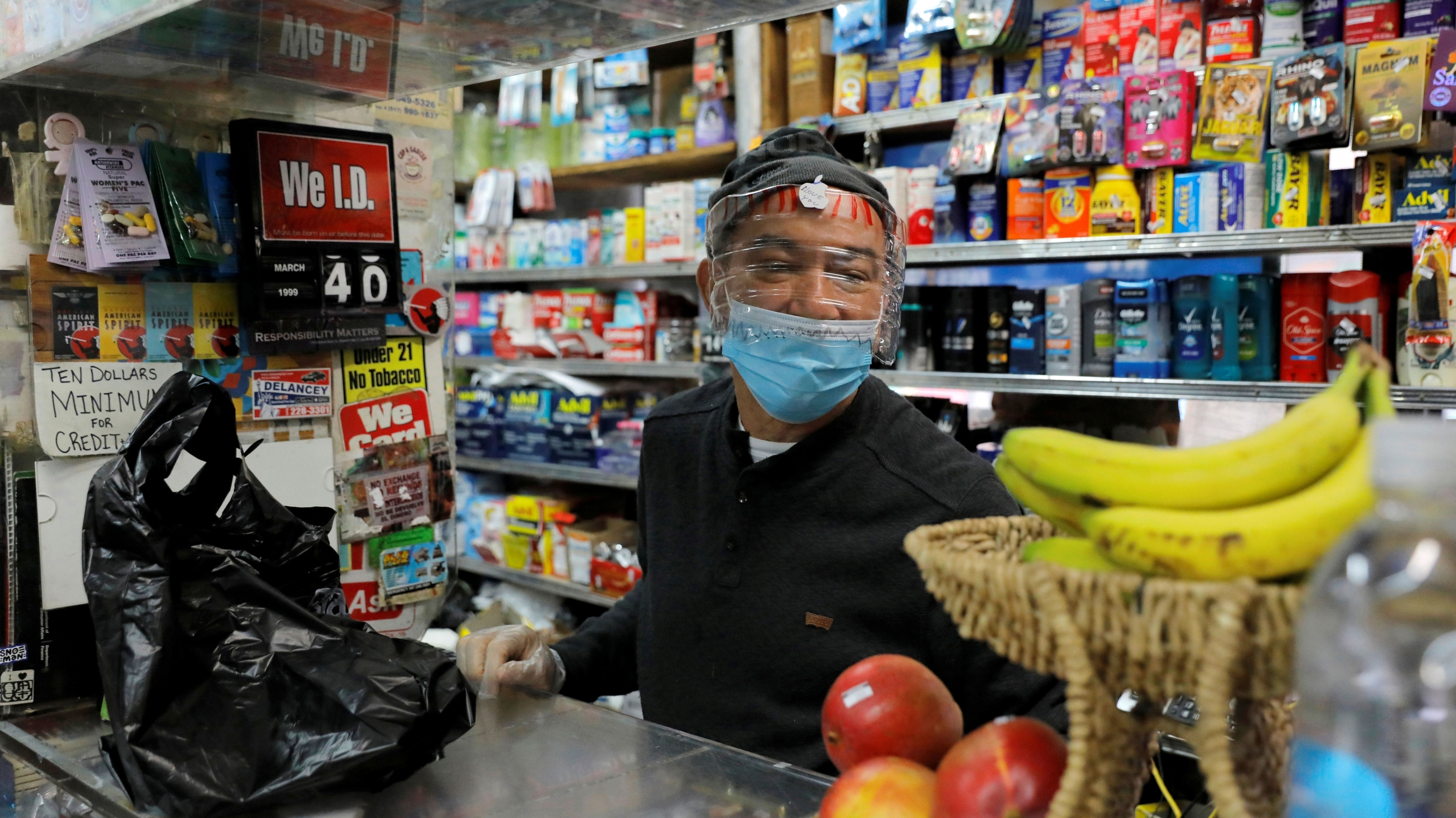 Bodega manager Rafael Perez wears a homemade face protector, fashioned from a water bottle, as he works in the Chinese Hispanic Grocery during the coronavirus disease (COVID-19) outbreak in New York City, New York, April 2, 2020.