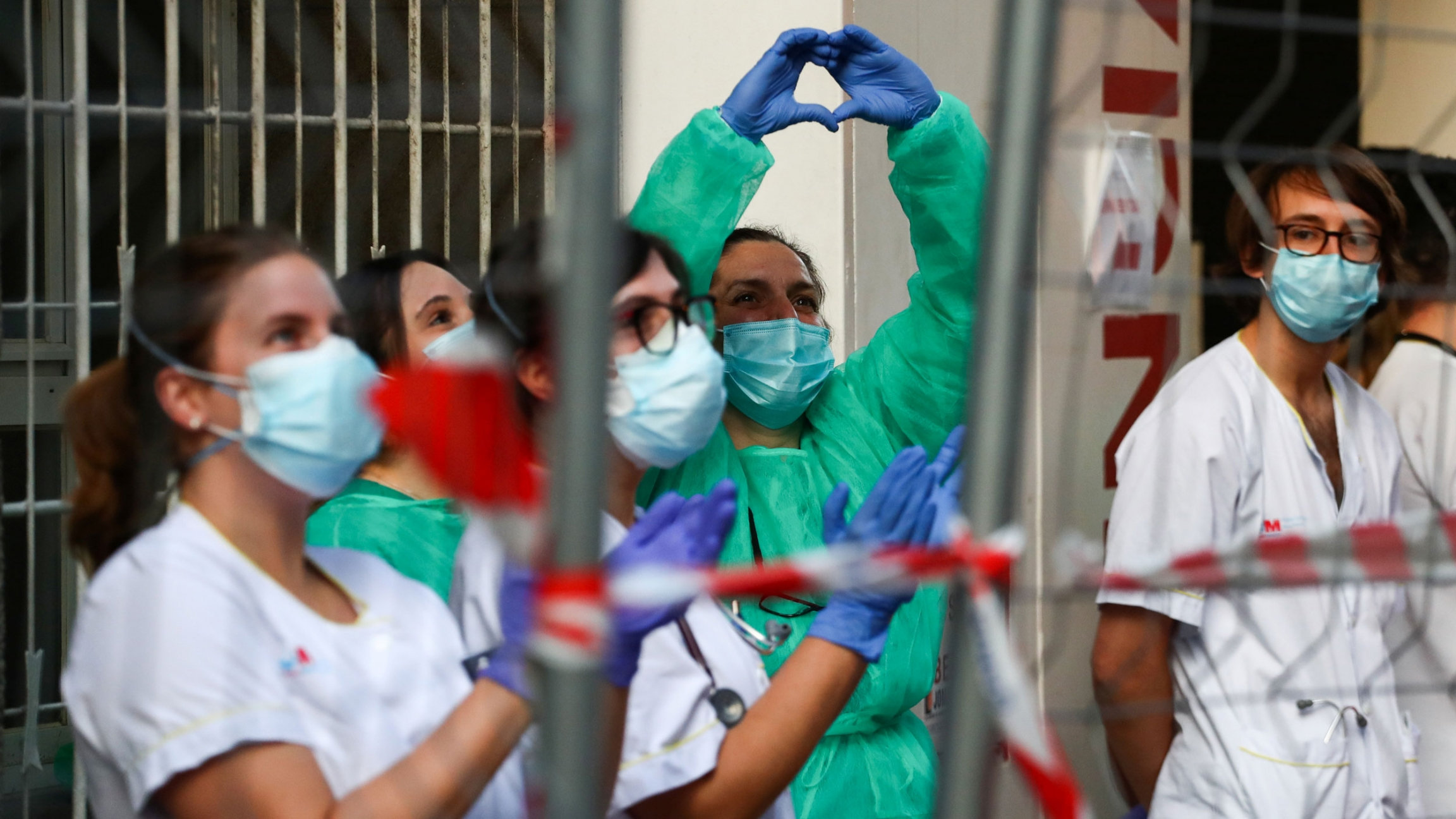 Several health care workers are shown wearing protective suits and one woman making a heart shape with her hands.
