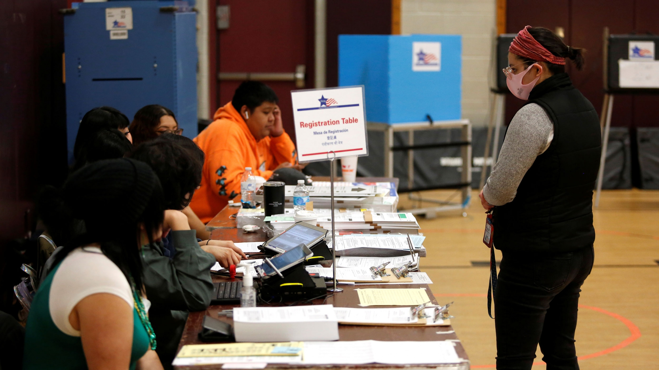 A voter stands at the registration table before receiving their ballot during the Democratic presidential primary election at Madero Middle School in Chicago, Illinois, March 17, 2020.
