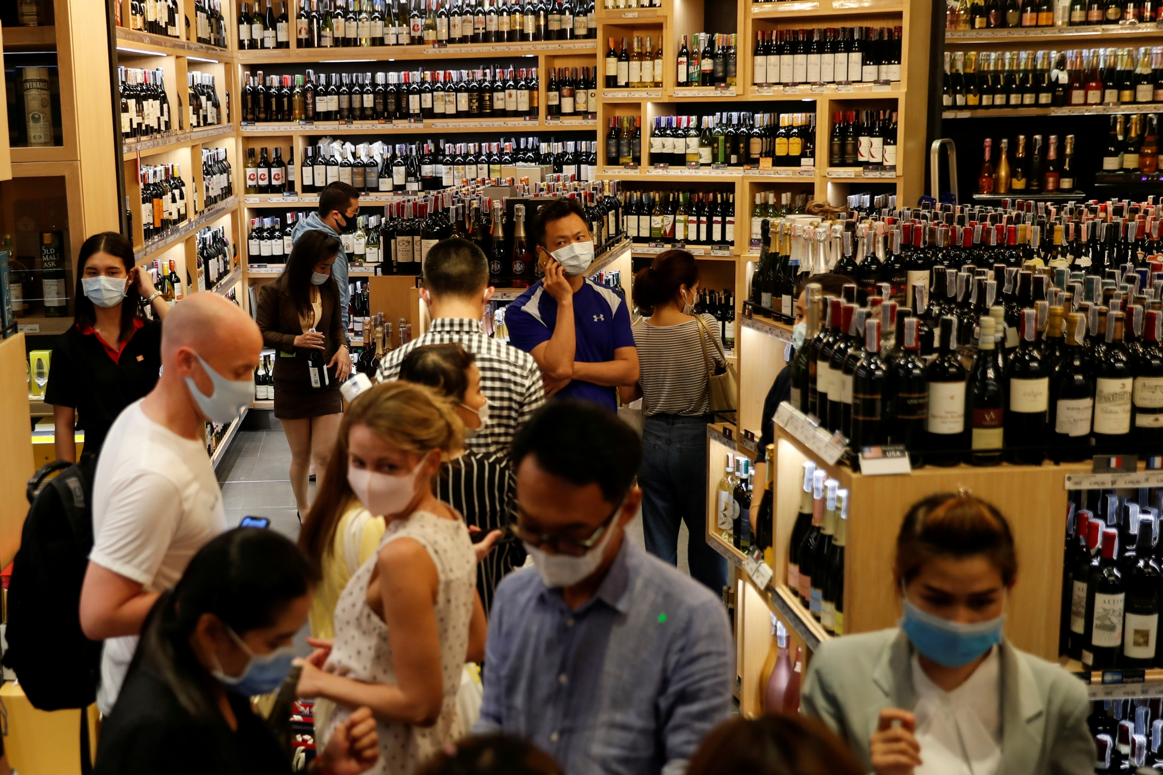 People line up inside a crowded liquor shop after Bangkok and several other provinces announced a 10-day ban on alcohol sale starting April 10 during the coronavirus outbreak in Bangkok, Thailand, April 9, 2020.