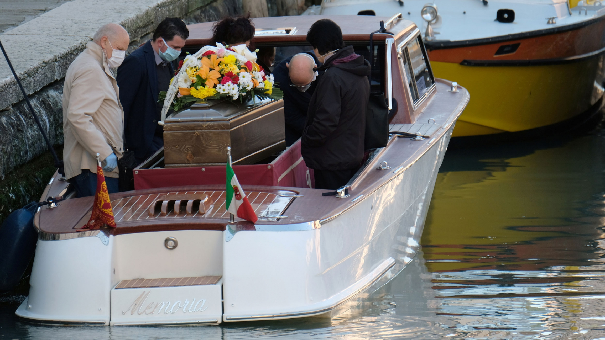 People gather around a coffin on a boat