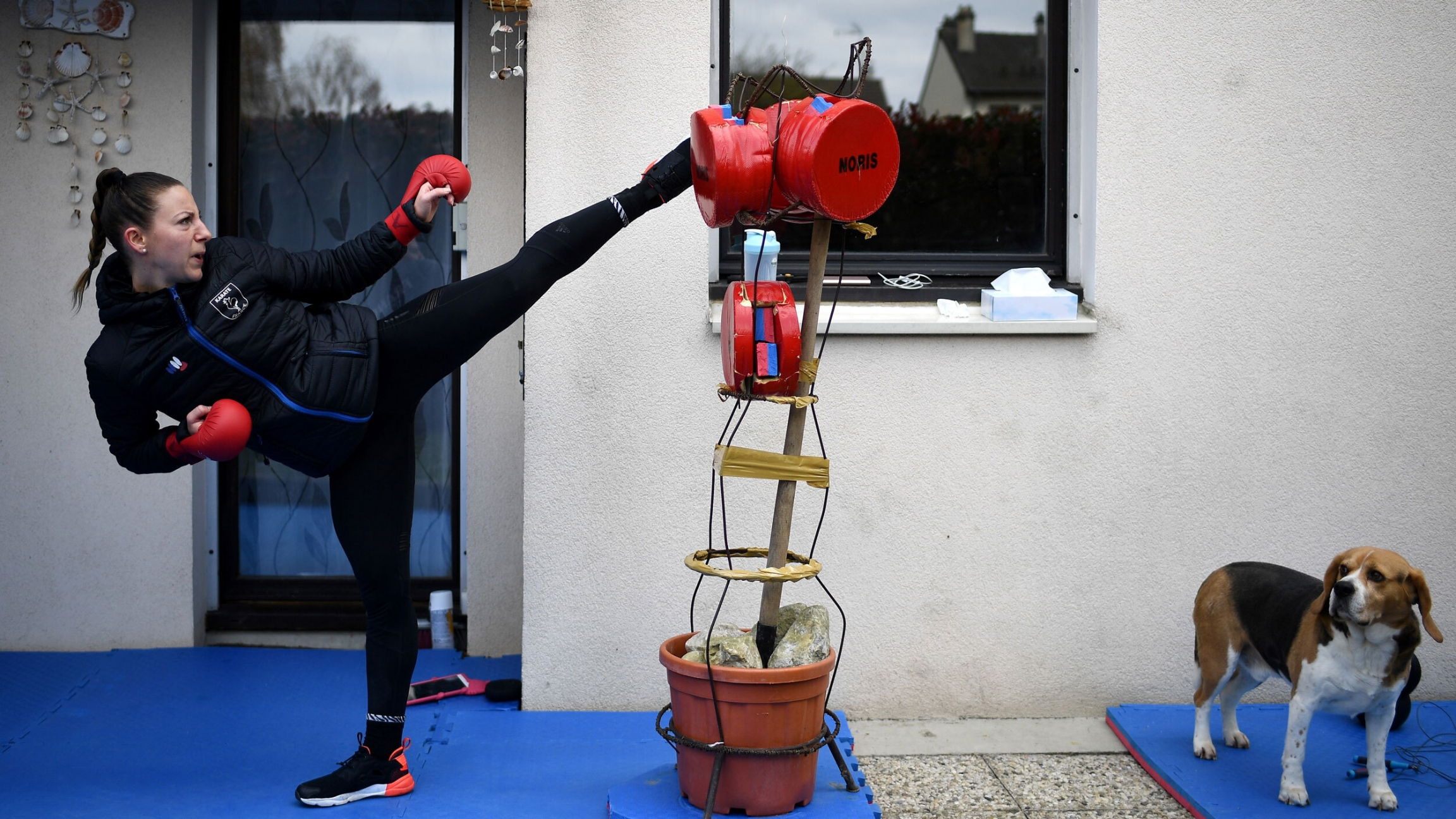 a woman in black gym clothes throws a high kick to a makeshift sparing partner